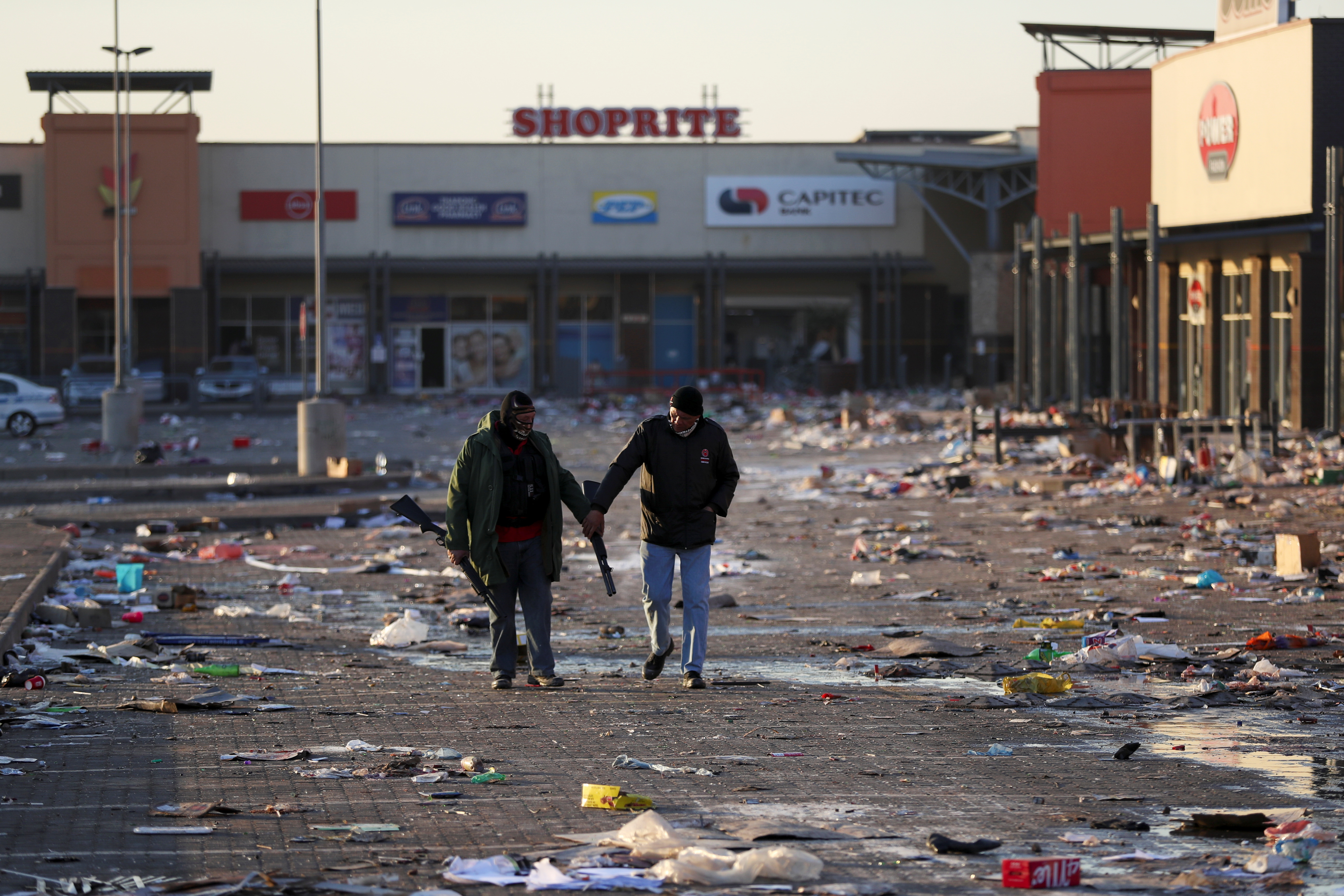Members of a private security walk at a looted shopping mall as the country deploys army to quell unrest linked to the jailing of former South African President Jacob Zuma, in Vosloorus, South Africa, July 14, 2021. REUTERS/Siphiwe Sibeko