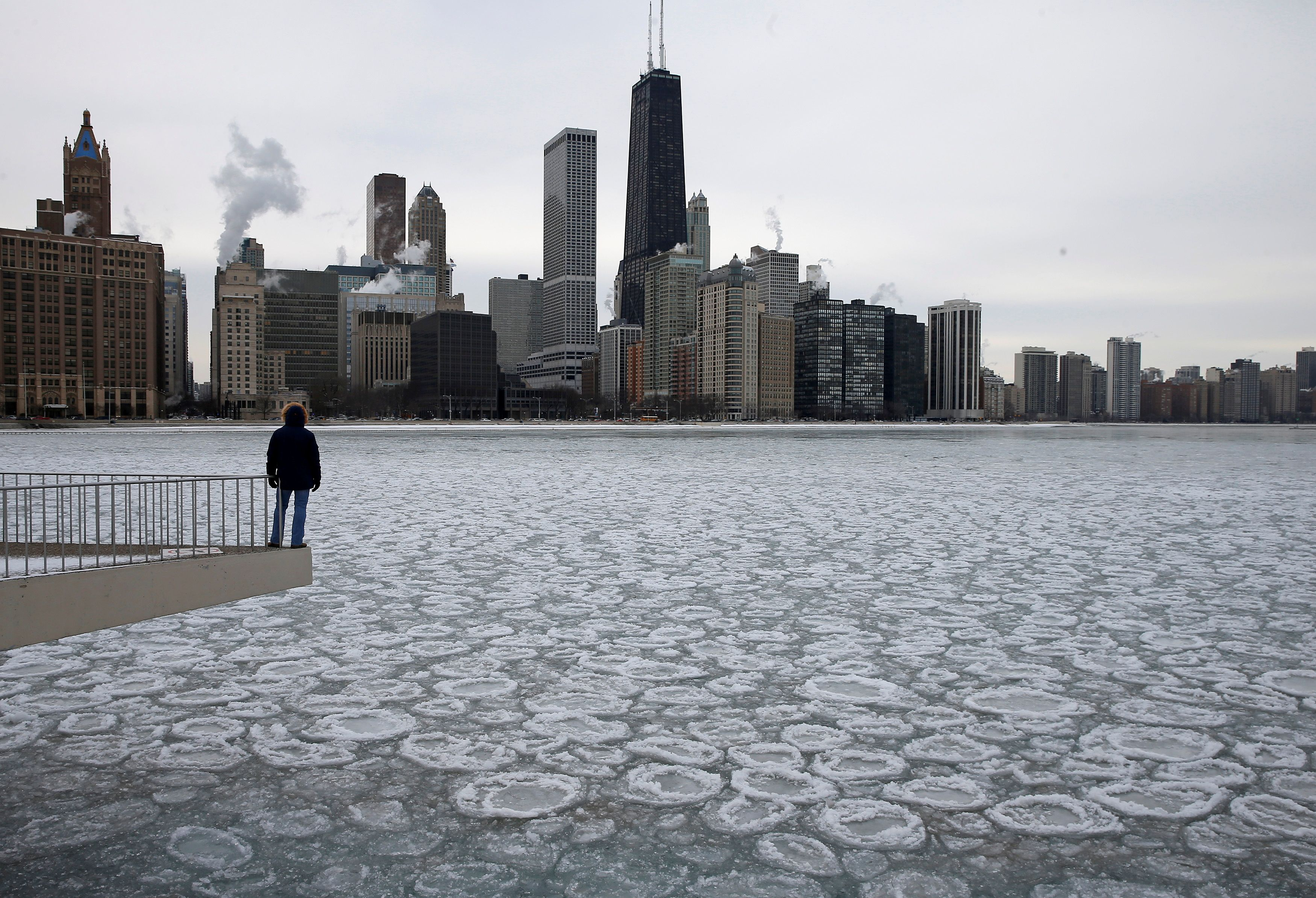 A man looks over the partially frozen Lake Michigan and the Chicago skyline, January 5, 2015.  REUTERS/Jim Young/File Photo