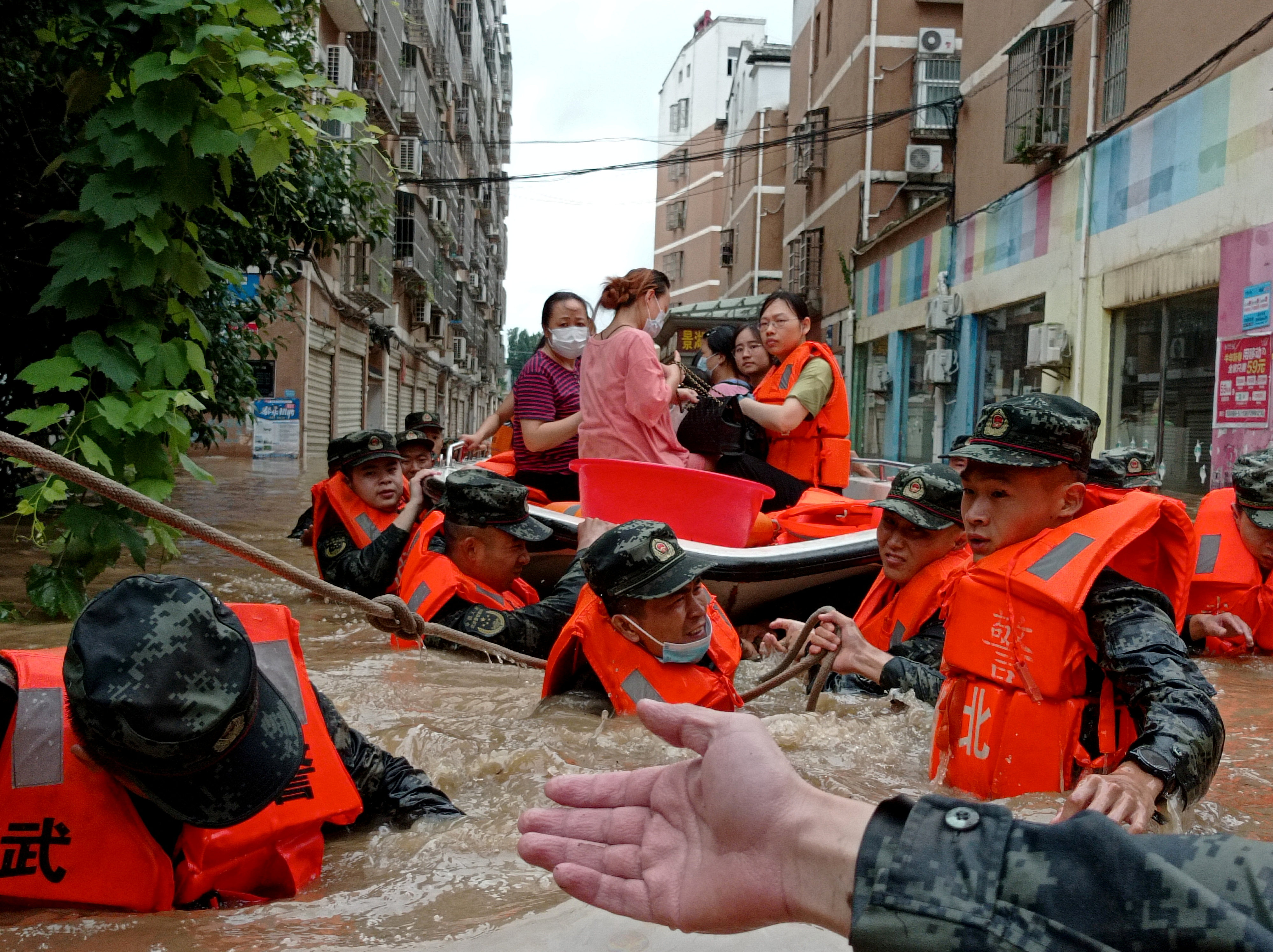 Paramilitary police officers evacuate residents stranded by floodwaters with a boat following heavy rainfall in Hedian town of Suizhou, Hubei province, China August 12, 2021. cnsphoto via REUTERS