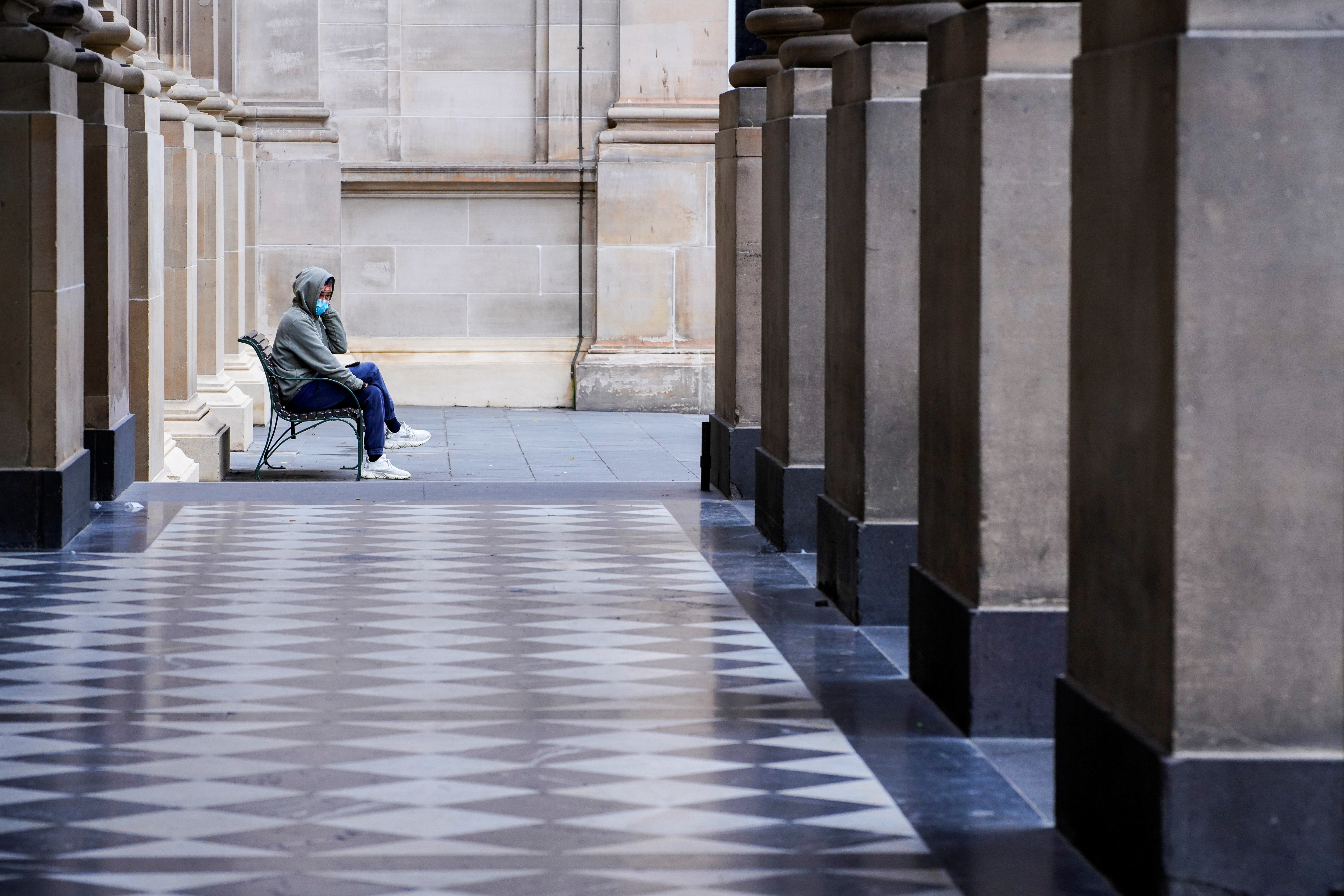 A lone man wearing a protective face mask sits at an unusually quiet State Library on the first day of a lockdown as the state of Victoria looks to curb the spread of a coronavirus disease (COVID-19) outbreak in Melbourne, Australia, July 16, 2021.  REUTERS/Sandra Sanders