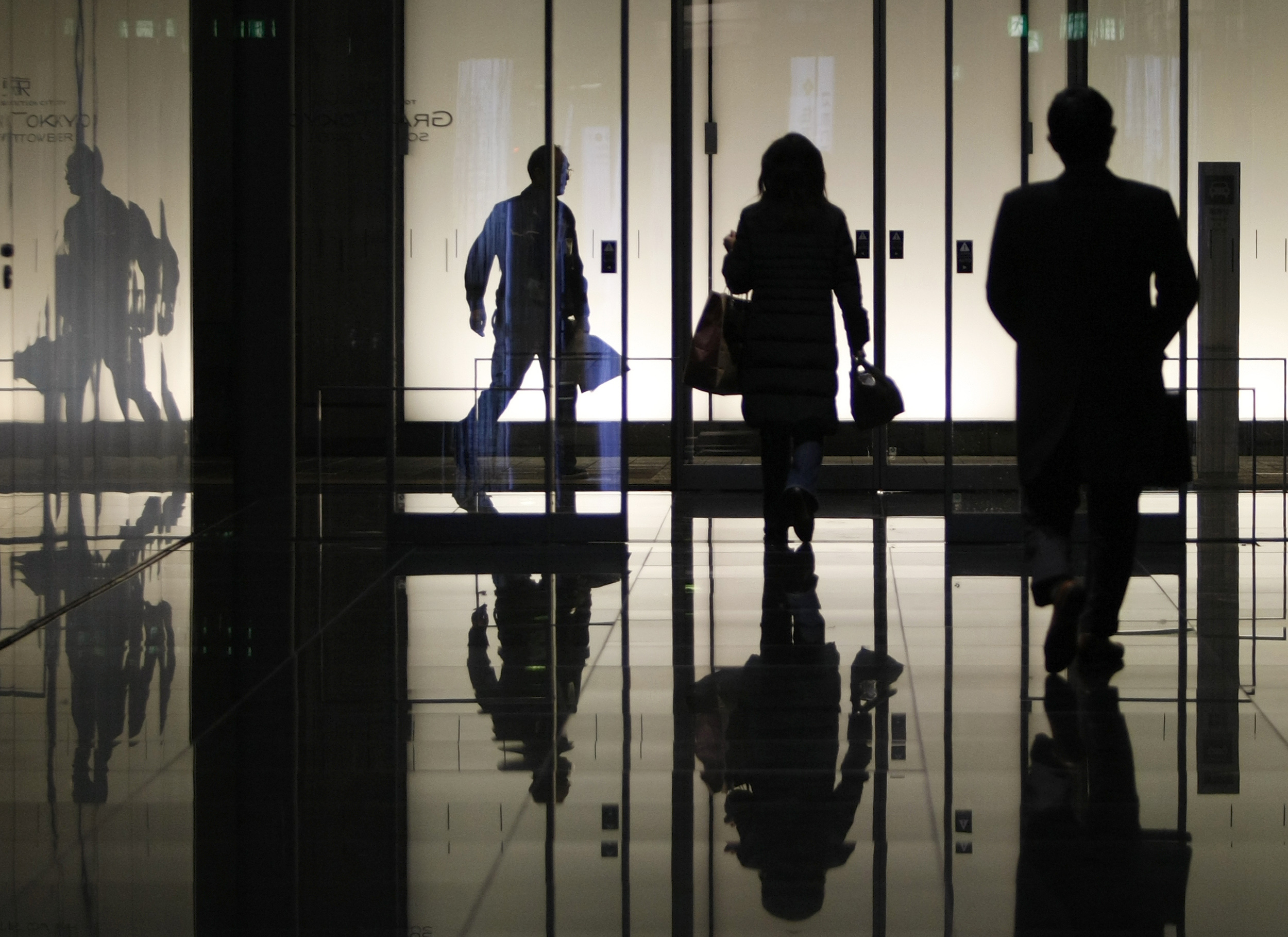 Pedestrians walk through an office building in Tokyo January 8, 2009. Deepening economic problems are forcing the government to prioritise spending to support the economy rather than steps to restore its tattered finances. REUTERS/Yuriko Nakao(JAPAN) - GM1E5181FTI01