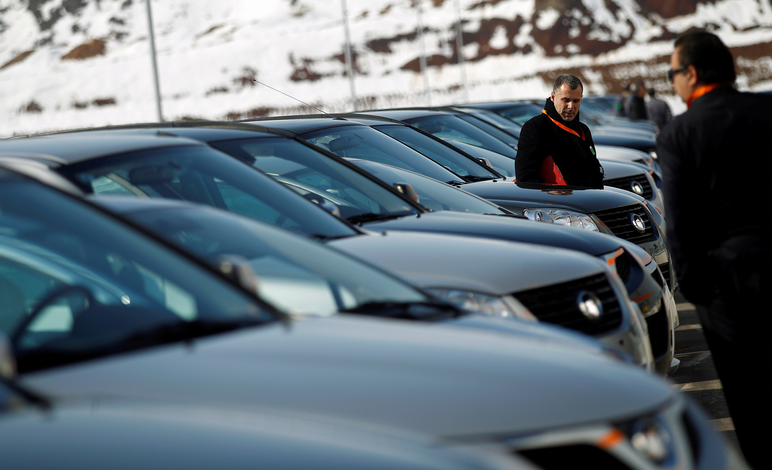 People look at a line of Great Wall cars parked in front of the newly opened car factory of Great Wall Motor Co near the town of Lovech, some 150 km (93 miles) north-east of Sofia February 21, 2012. REUTERS/Stoyan Nenov/File Photo