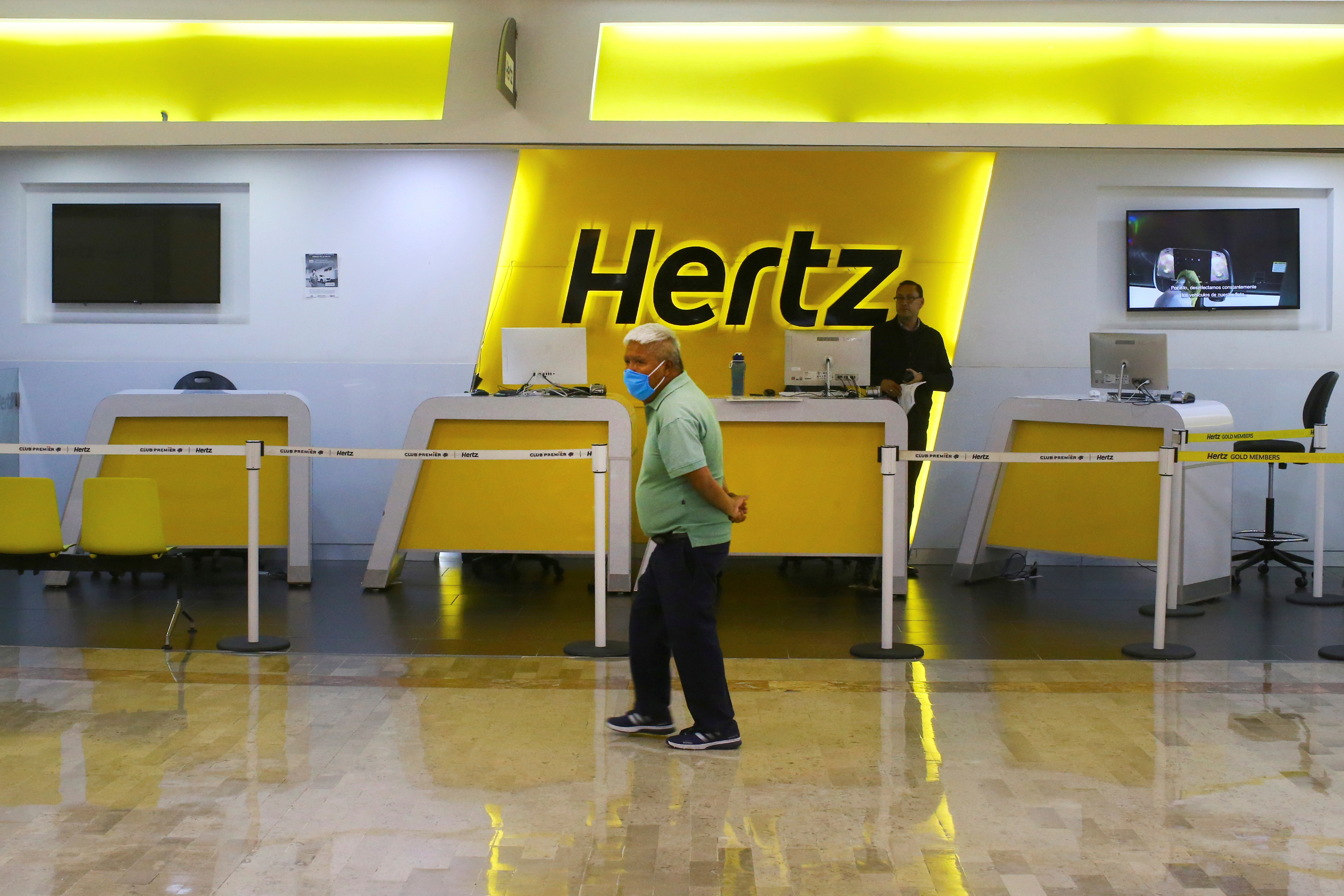 A passenger wearing a protective mask passes in front of a counter of the car rental company Hertz in Mexico City, Mexico, June 11, 2020. REUTERS/Edgard Garrido