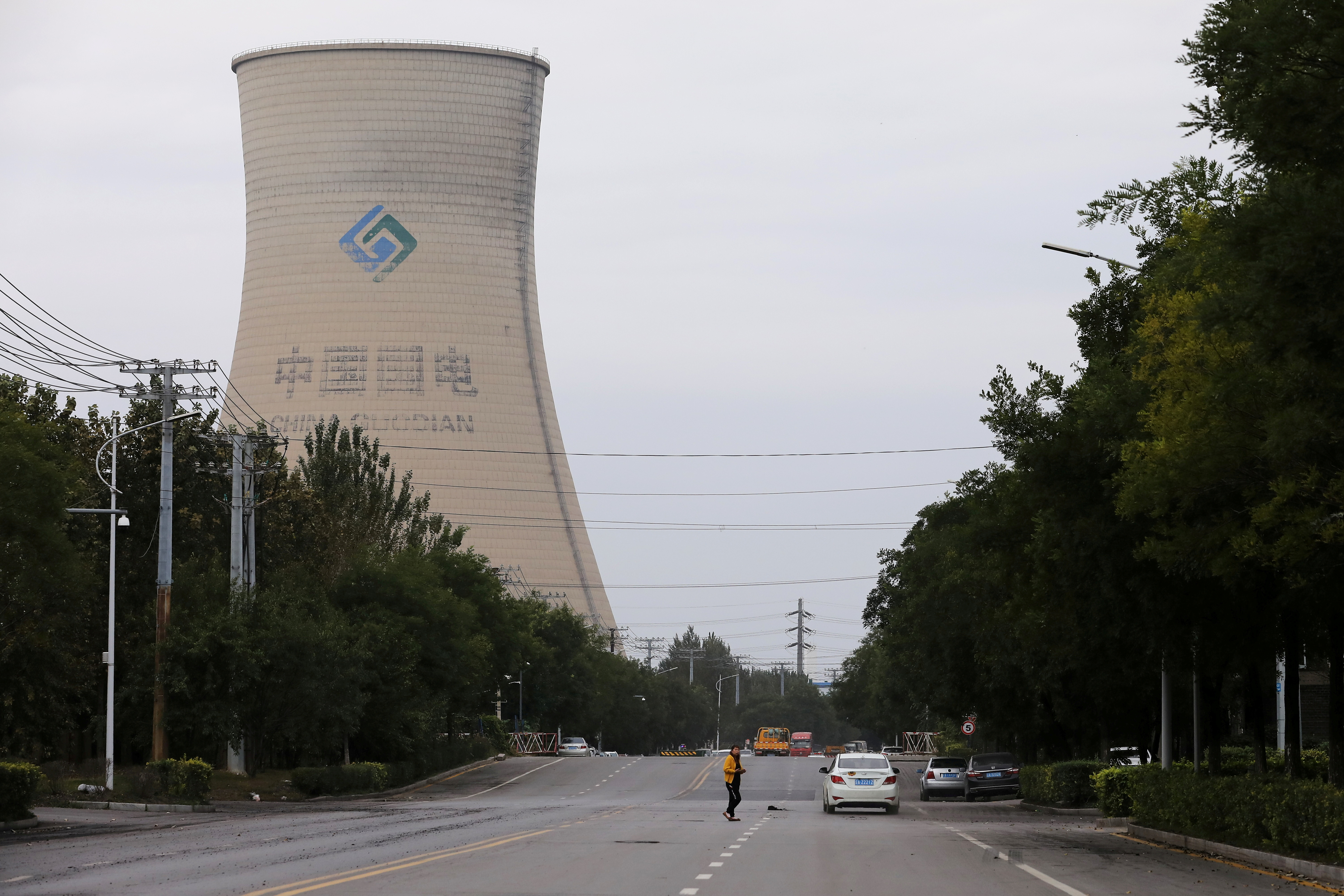 A person walks near a China Energy coal-fired power plant in Shenyang, Liaoning province, China September 29, 2021. REUTERS/Tingshu Wang