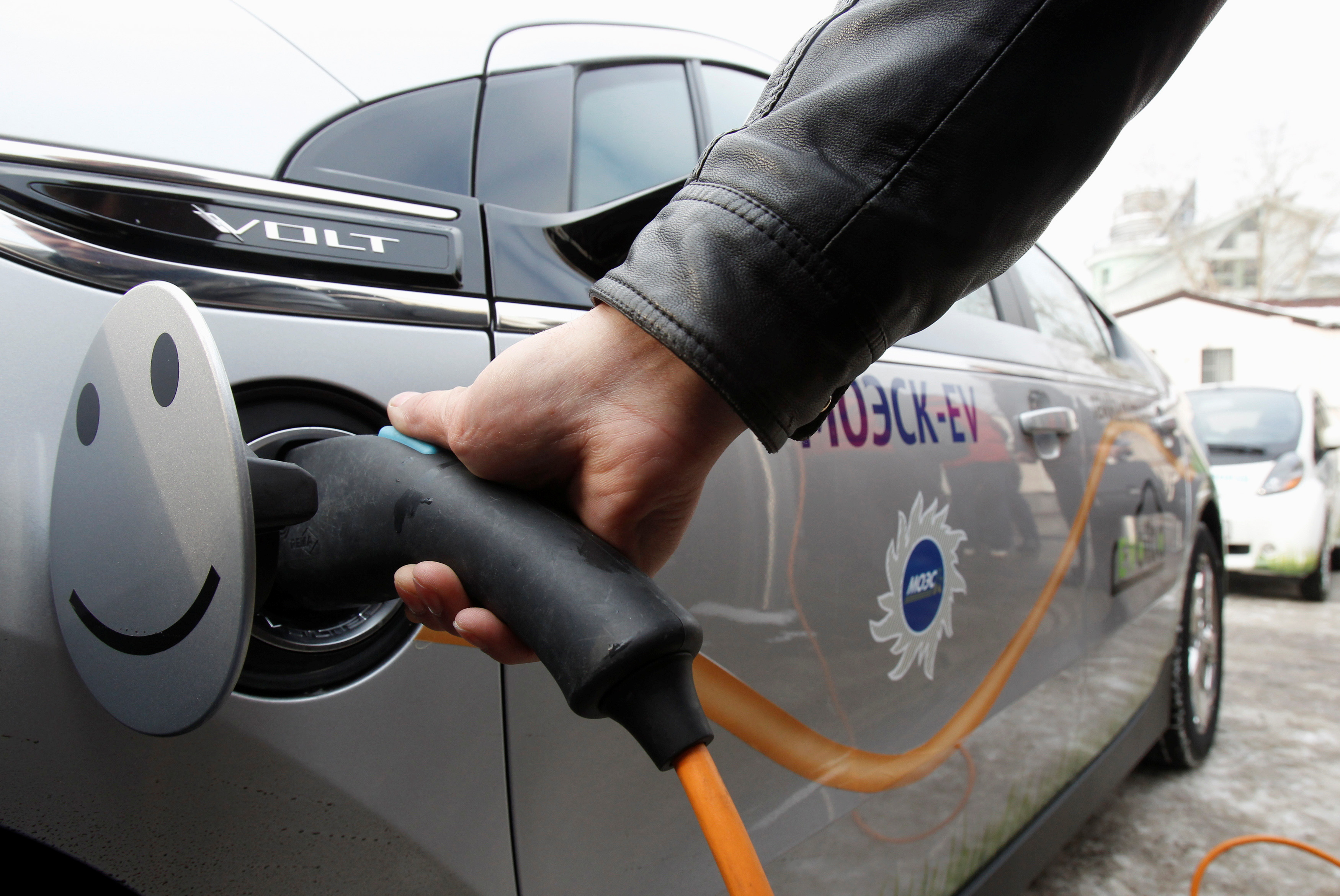 A man charges an electric car during a demonstration ceremony to launch a charging station, owned by the Moscow United Electric Grid Company (MOESK), in Moscow February 28, 2012. REUTERS/Sergei Karpukhin/File Photo