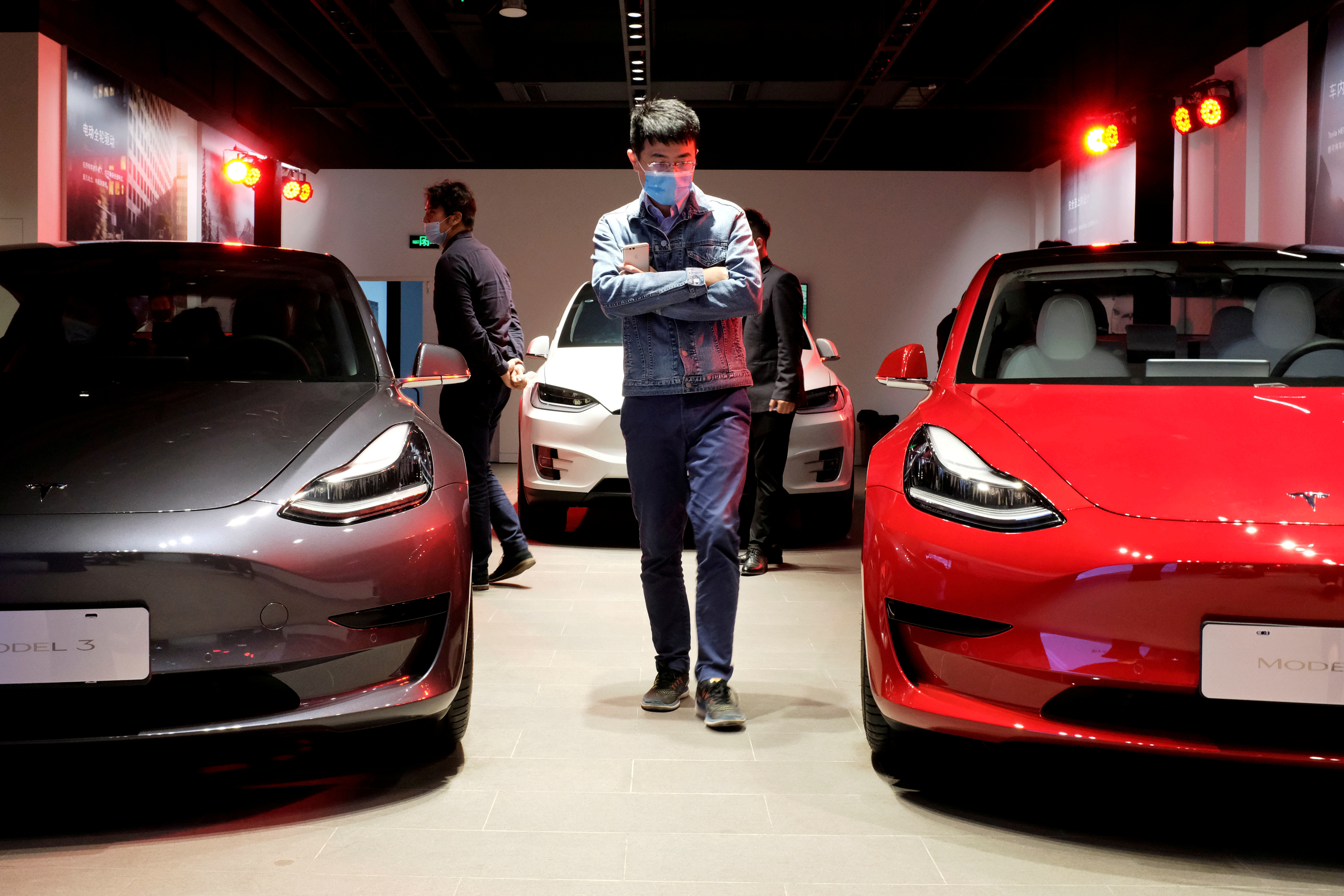 A man wearing a face mask following the coronavirus disease (COVID-19) outbreak walks by Tesla Model 3 sedans and Tesla Model X sport utility vehicle at a new Tesla showroom in Shanghai, China May 8, 2020. REUTERS/Yilei Sun/File Photo