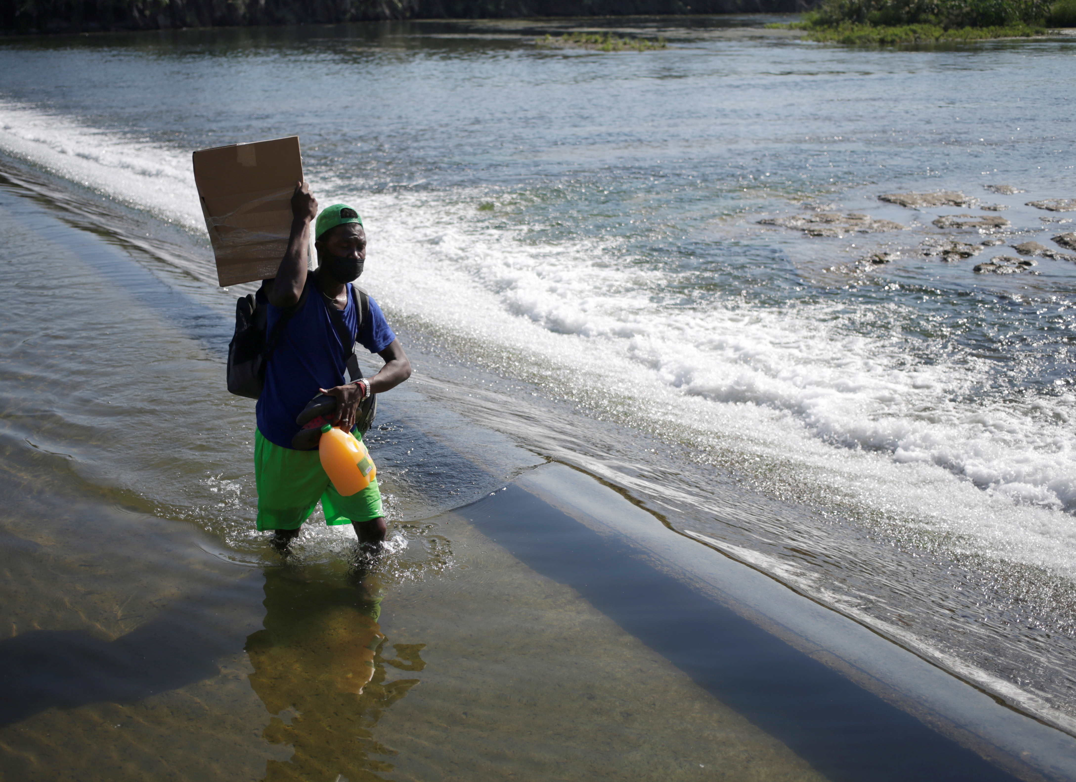 Migrant asylum seeker Jean Agenord walks back across the Rio Grande river, which divides the border between Ciudad Acuna, Mexico and Del Rio, Texas, U.S., after being rejected by Texas police officers, after he tried to cross into the U.S. with his family, as seen from Ciudad Acuna, in Ciudad Acuna, Mexico September 19, 2021. REUTERS/Daniel Becerril
