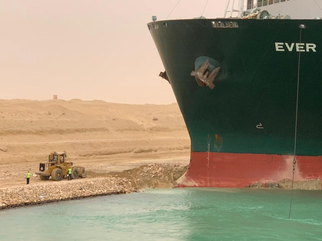 Workers are seen next to a container ship which was hit by strong wind and ran aground in Suez Canal, Egypt March 24, 2021. Suez Canal Authority/Handout via REUTERS