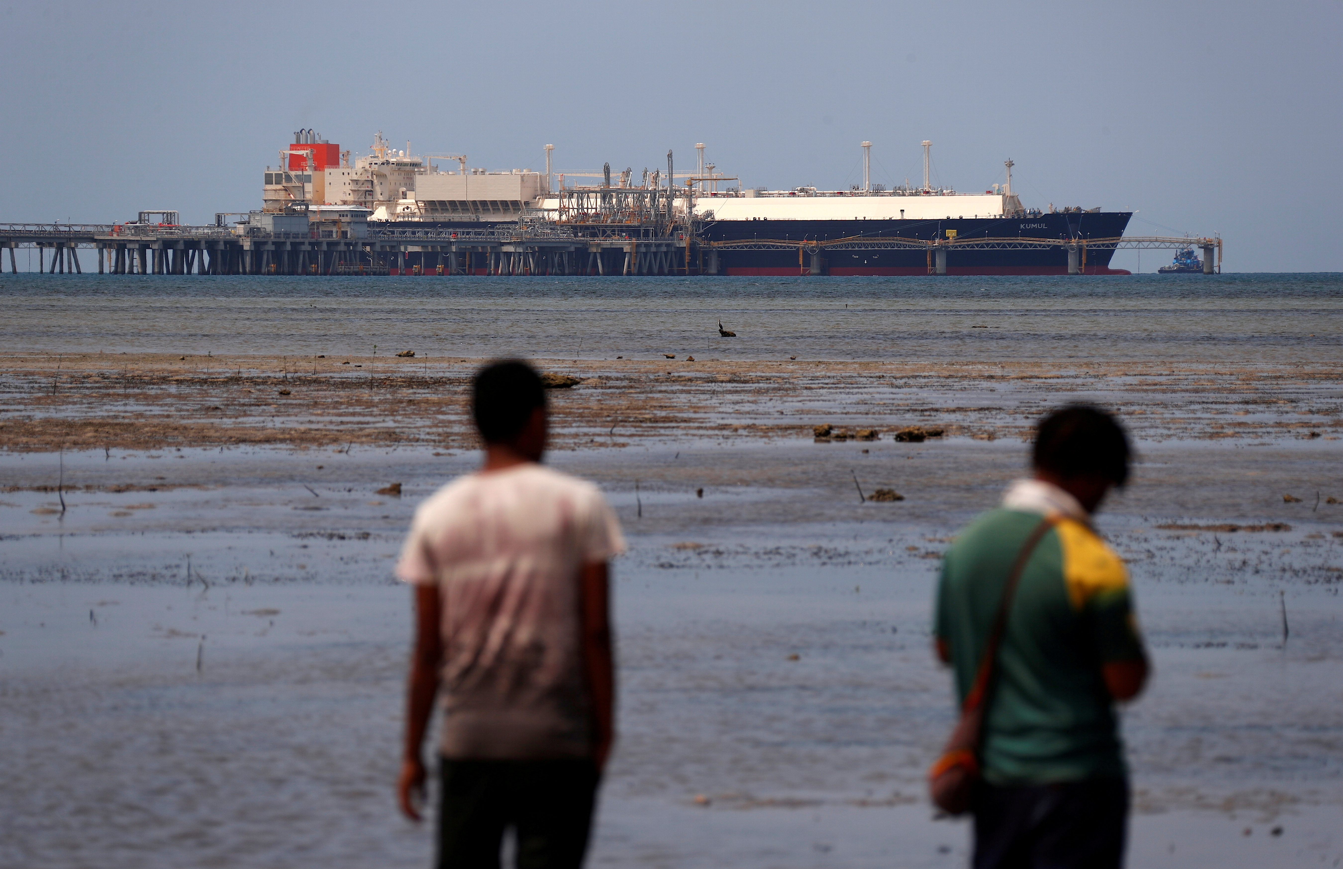 Locals walk along a small beach where a Liquefied Natural Gas (LNG) carrier called Kumul is docked at the marine facility of the ExxonMobil PNG Limited operated LNG plant at Caution Bay, located on the outskirts of Port Moresby in Papua New Guinea, November 19, 2018. REUTERS/David Gray/File Photo