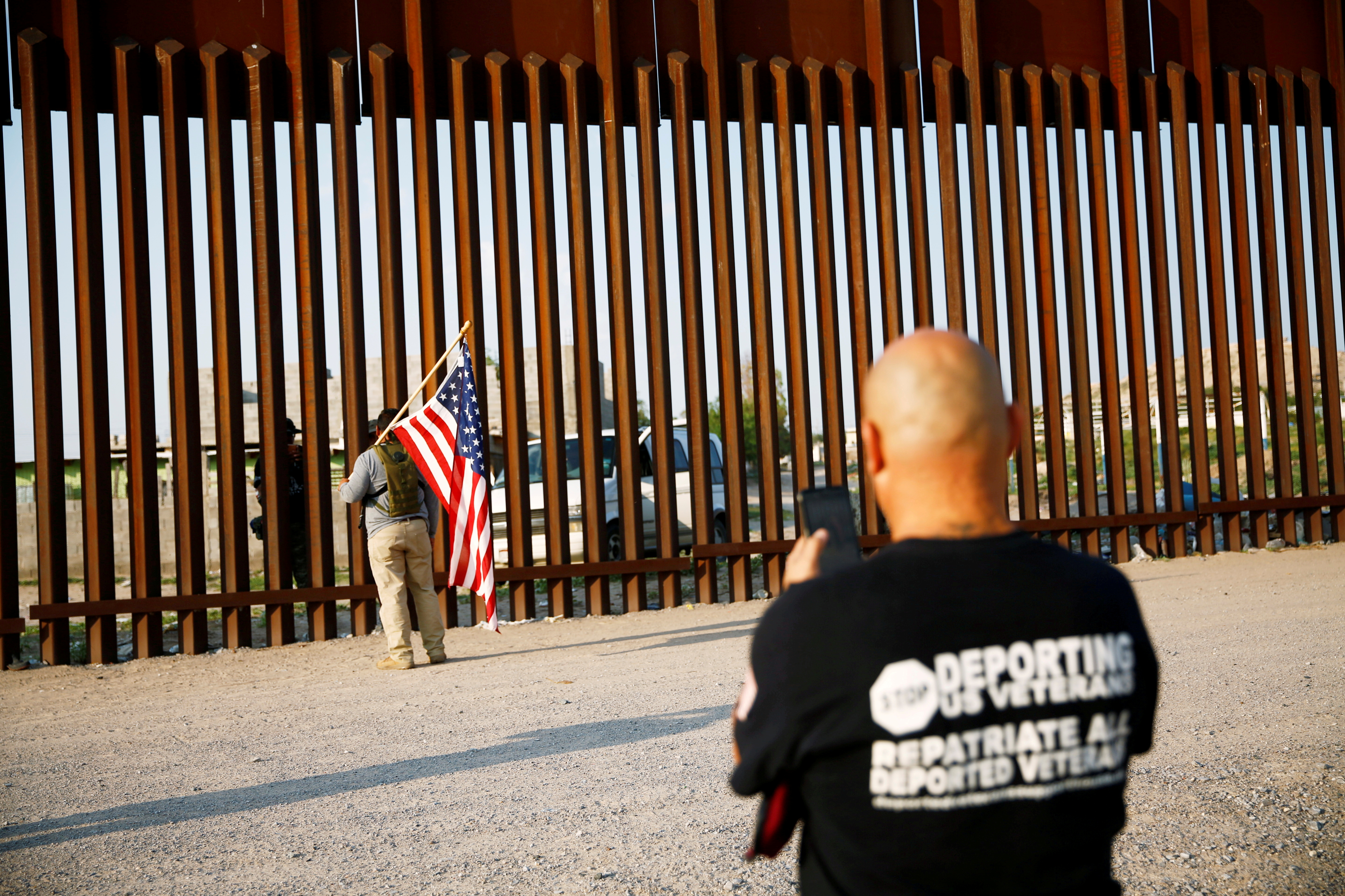 Ramon Castro, a U.S. Marine veteran, speaks through the border wall with military veterans as he takes part in the