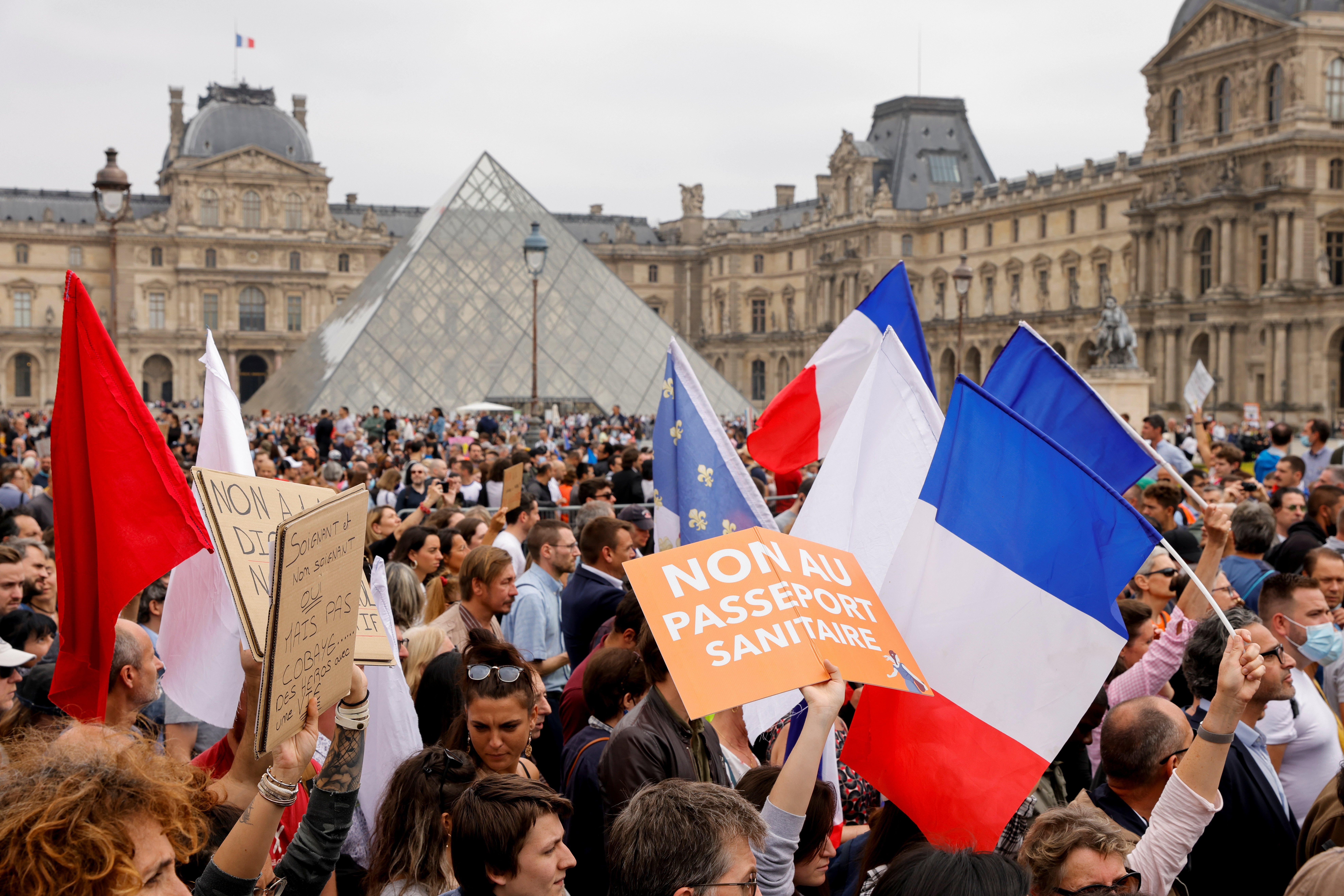 Demonstrators walk past Pyramide du Louvre during a protest against the new measures announced by French President Emmanuel Macron to fight the coronavirus disease (COVID-19) outbreak, in Paris, France, July 17, 2021. REUTERS/Pascal Rossignol