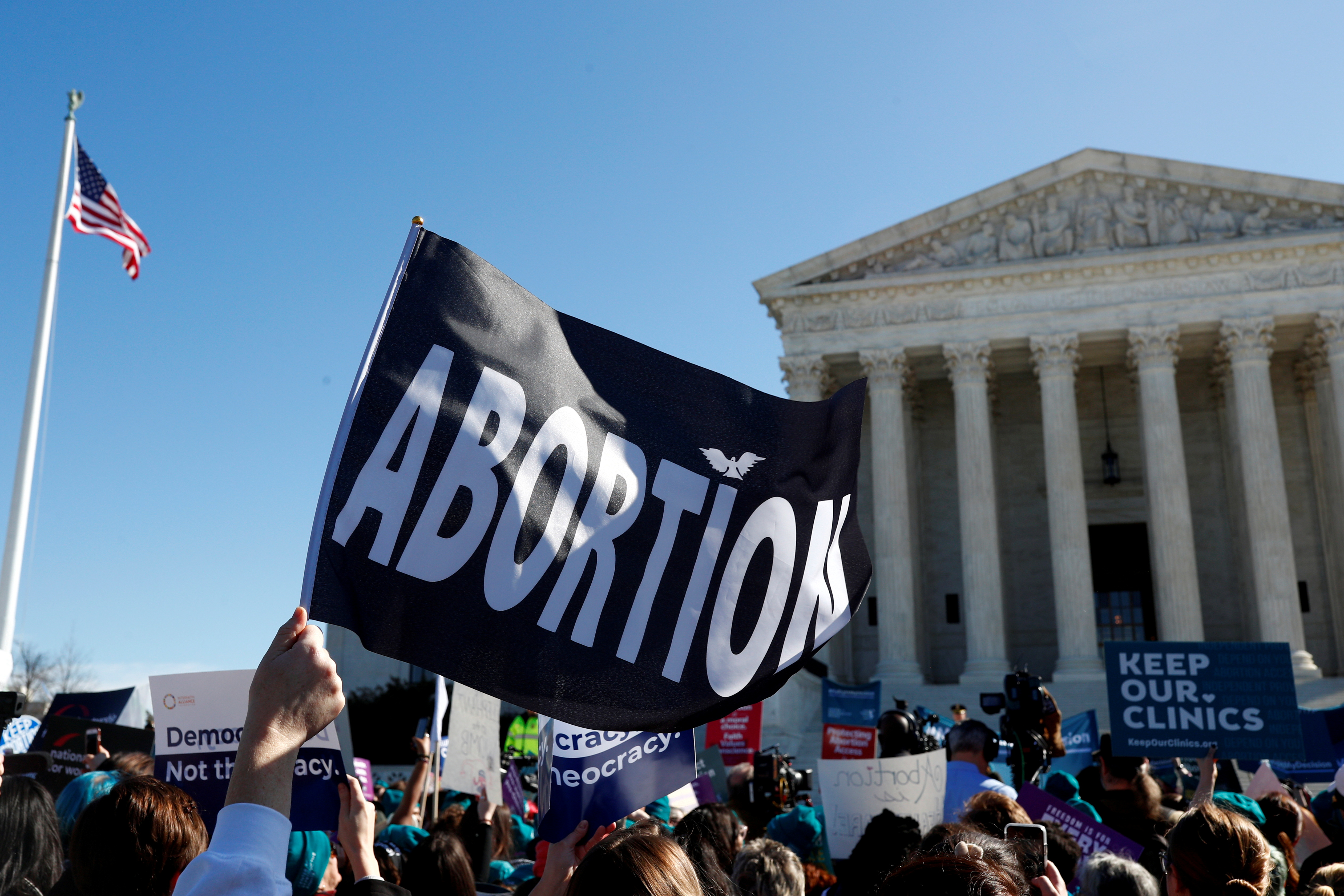 A demonstrator holds up an abortion flag outside of the U.S. Supreme Court as justices hear a major abortion case on the legality of a Republican-backed Louisiana law that imposes restrictions on abortion doctors, on Capitol Hill in Washington, U.S., March 4, 2020.  REUTERS/Tom Brenner/File Photo