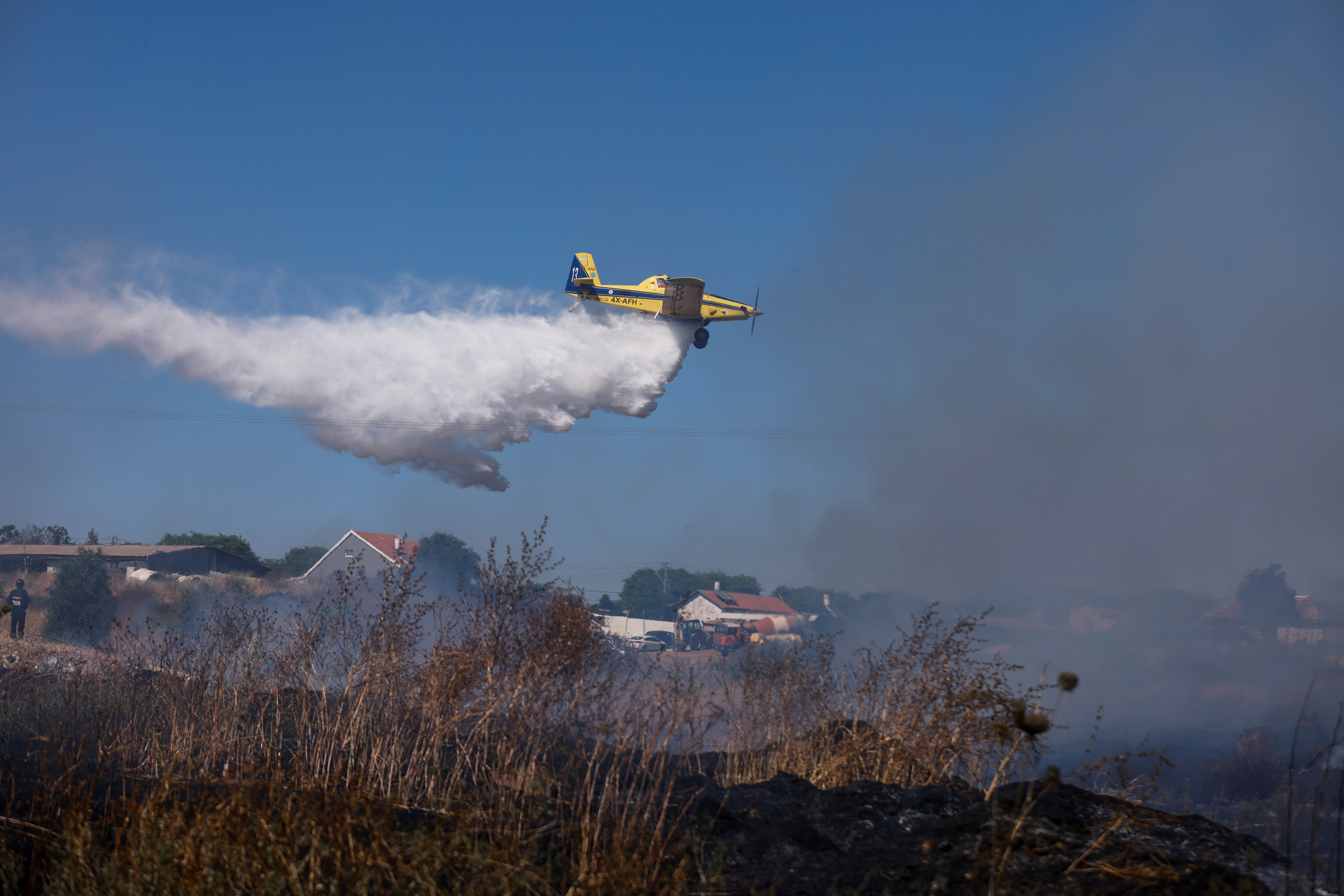 An Israeli firefighting plane extinguishes a fire on a field of wheat after a rocket launched from the Gaza Strip landed near homes in Moshav Zohar, Israel May 13, 2021. REUTERS/Amir Cohen