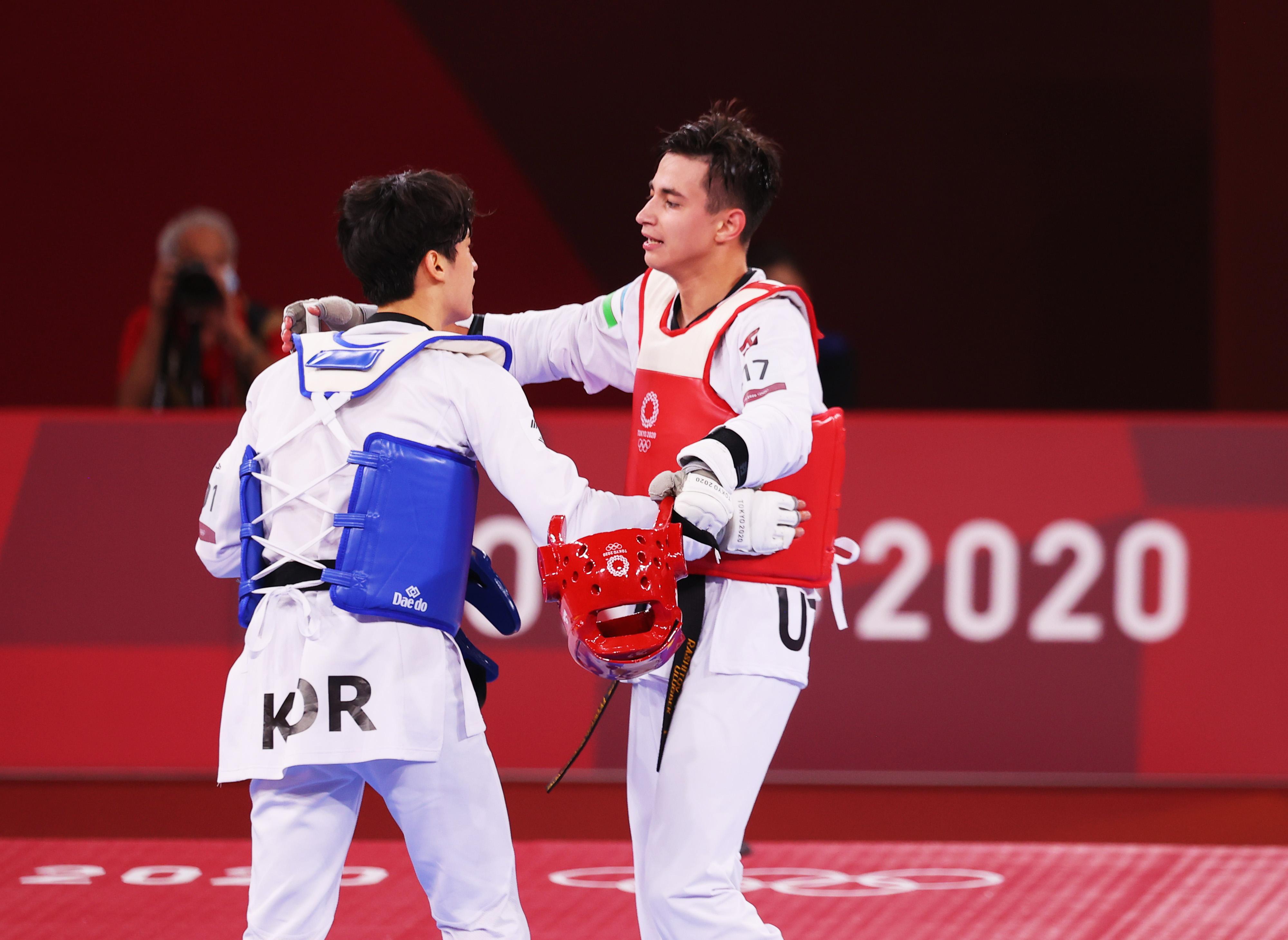 Tokyo 2020 Olympics - Taekwondo - Men's Featherweight 58-68kg - Last 16 - Makuhari Messe Hall A, Chiba, Japan - July 25, 2021. Ulugbek Rashitov of Uzbekistan and Lee Dae-Hoon of South Korea embrace after competing REUTERS/Murad Sezer