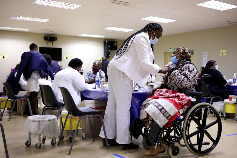 A woman receives a dose of a coronavirus disease (COVID-19) vaccine, as South Africa rolls out the coronavirus disease (COVID-19) vaccination to the elderly at the Munsieville Care for the Aged Centre outside Johannesburg, South Africa May 17, 2021. REUTERS/Siphiwe Sibeko/File Photo/File Photo