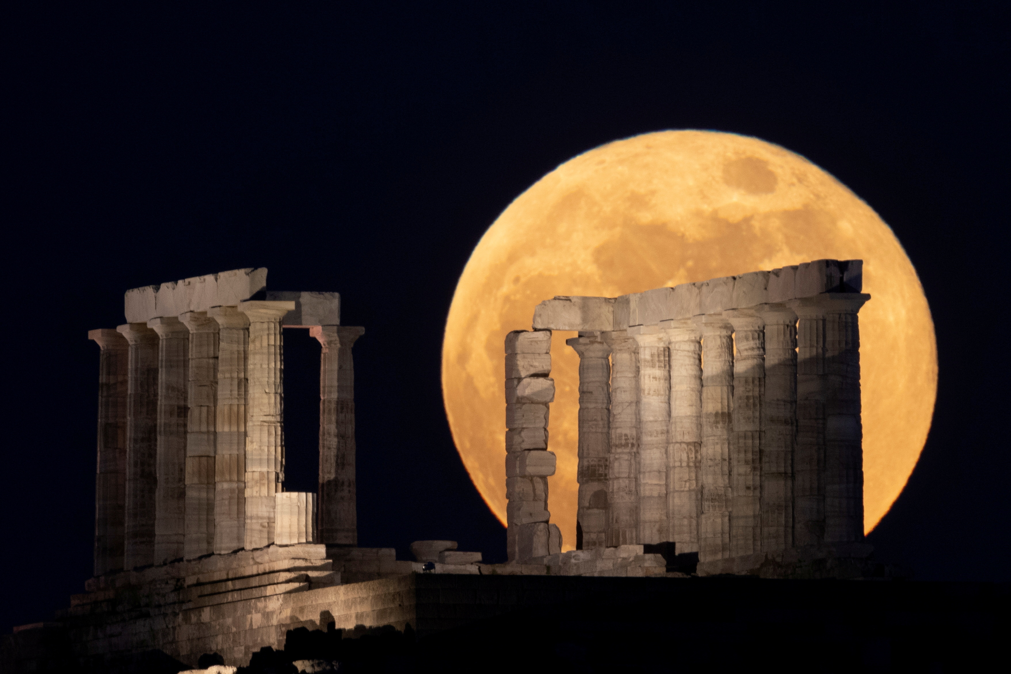 """The full moon, known as the """"Super Flower Moon"""" rises over the Temple of Poseidon in Cape Sounion, near Athens, Greece, May 26, 2021. REUTERS/Alkis Konstantinidis"""
