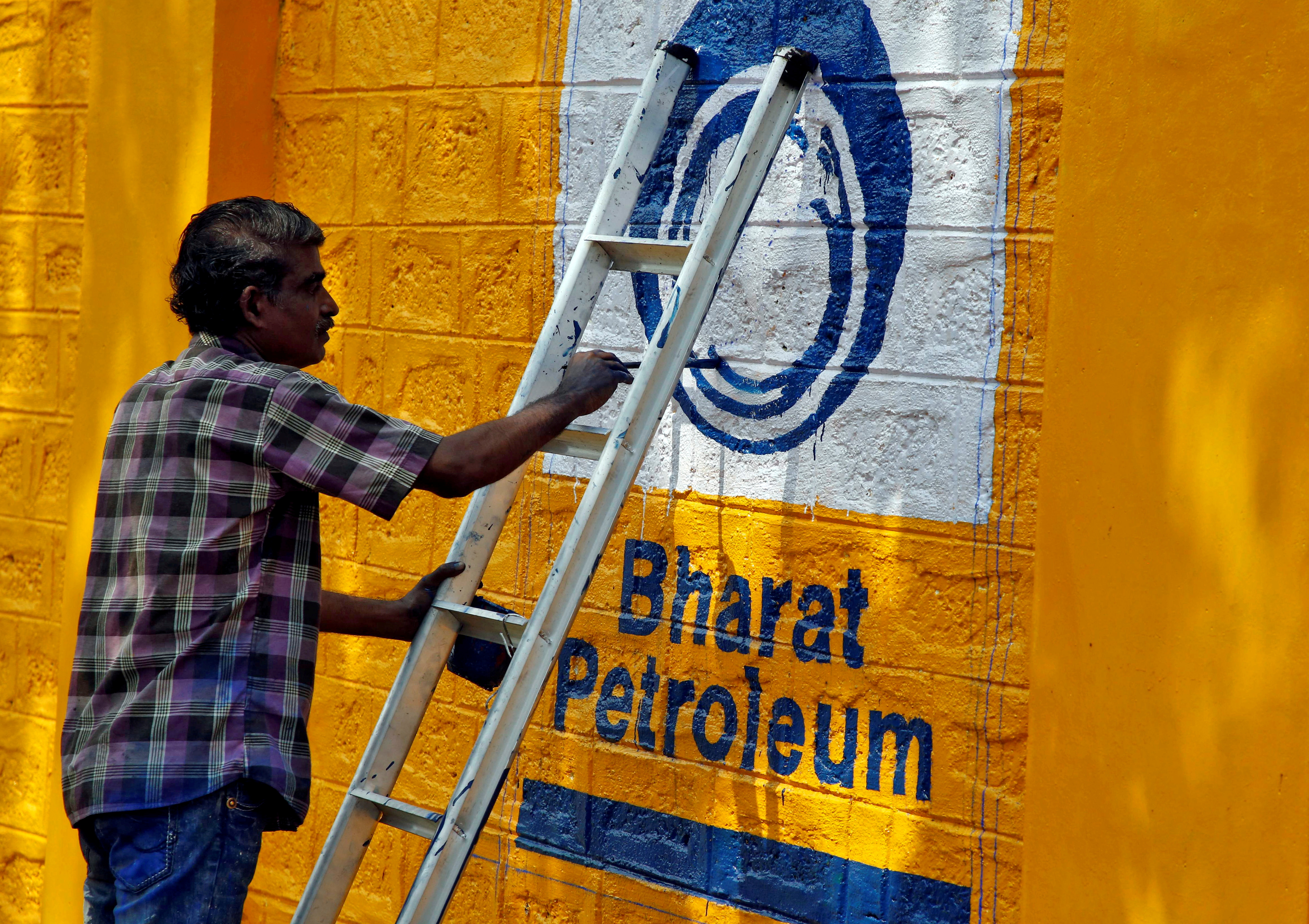 A man paints the logo of oil refiner Bharat Petroleum Corp (BPCL) on a wall on the outskirts of Kochi, India, November 21, 2019. REUTERS/Sivaram V
