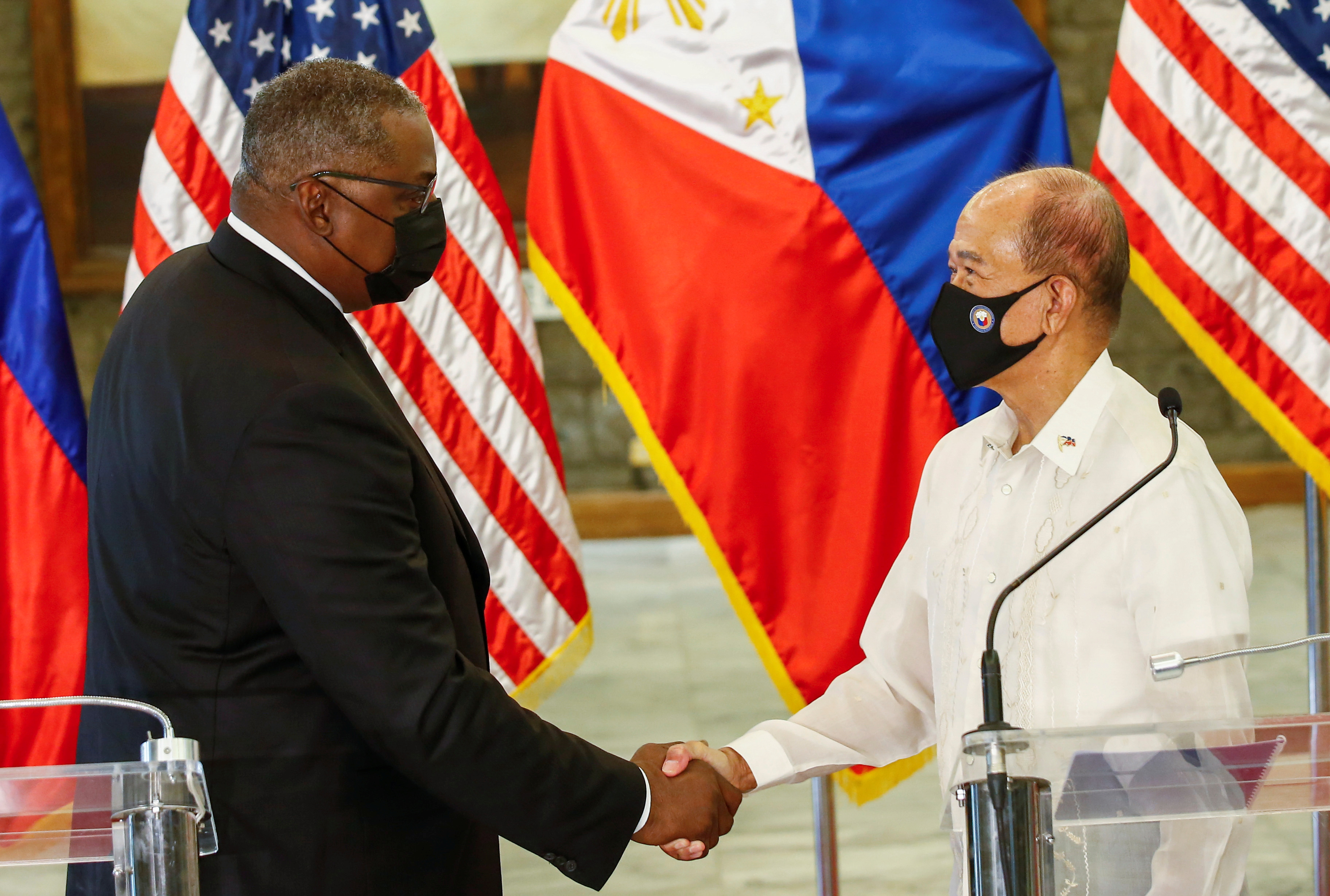 United States Defense Secretary Lloyd Austin (L) and Philippines' Defense Secretary Delfin Lorenzana (R) shake hands after a bilateral meeting at Camp Aguinaldo military camp in Quezon City, Metro Manila, Philippines, July 30, 2021. Rolex Dela Pena/Pool via Reuters