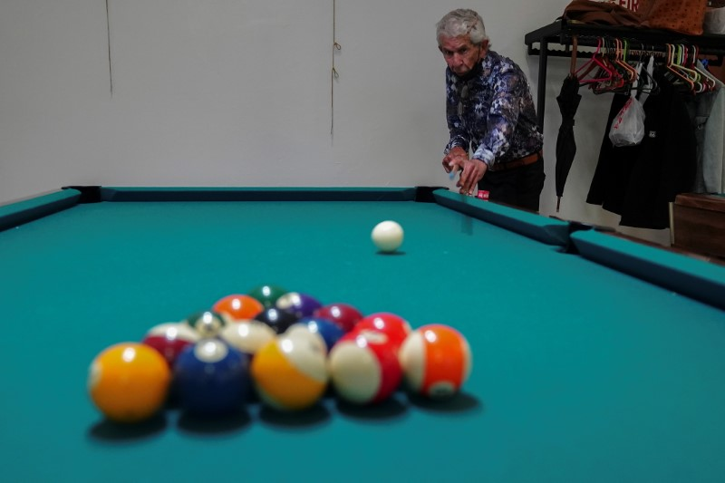 A man shoots the cue ball to break as he plays billiards at the S.T.A.R. Senior Center in New York City, New York, U.S., June 14, 2021. REUTERS/Carlo Allegri