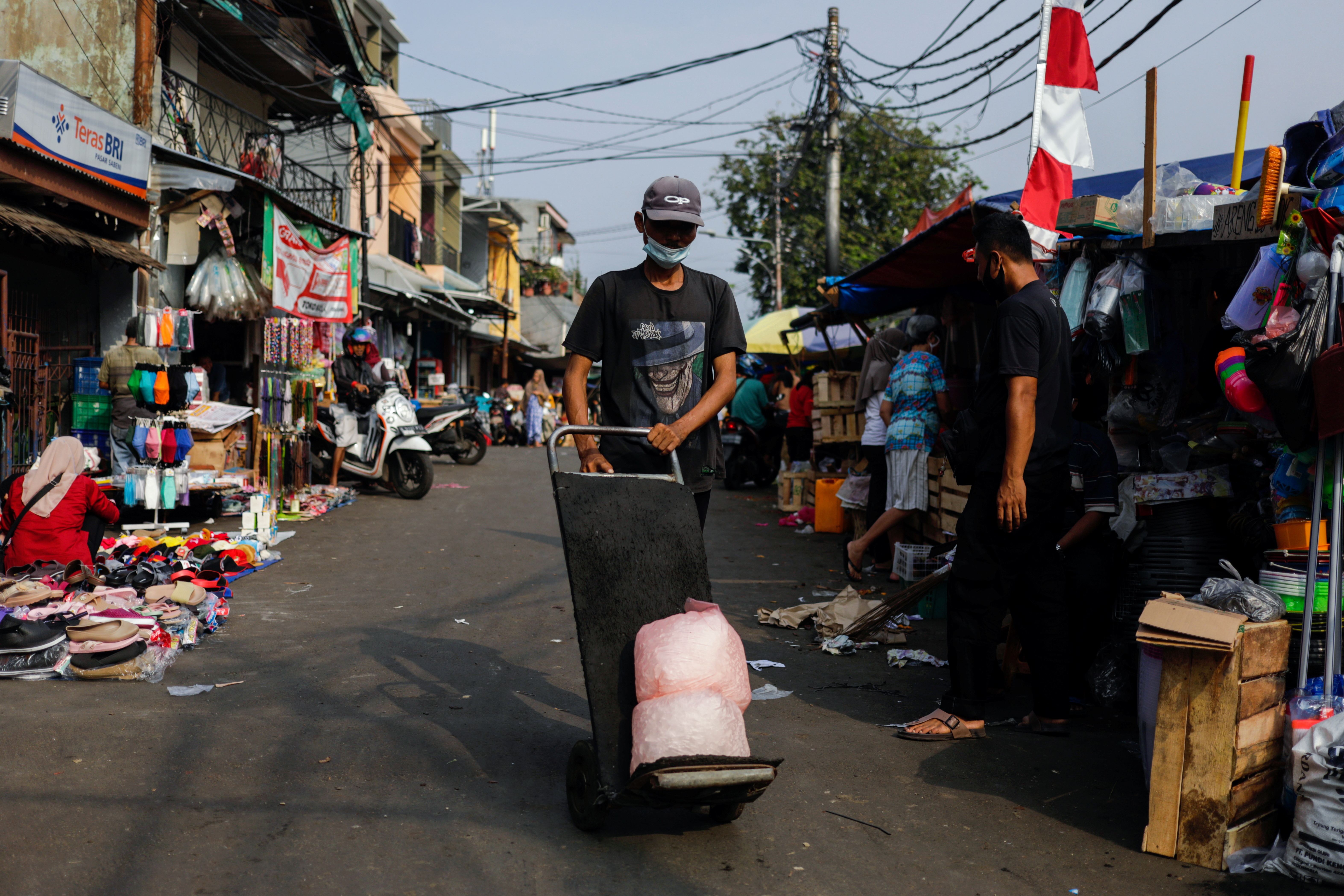 A man wearing a protective mask pushes a trolley at a traditional market amid the coronavirus disease (COVID-19) outbreak, in Jakarta, Indonesia, July 24, 2021. REUTERS/Willy Kurniawan