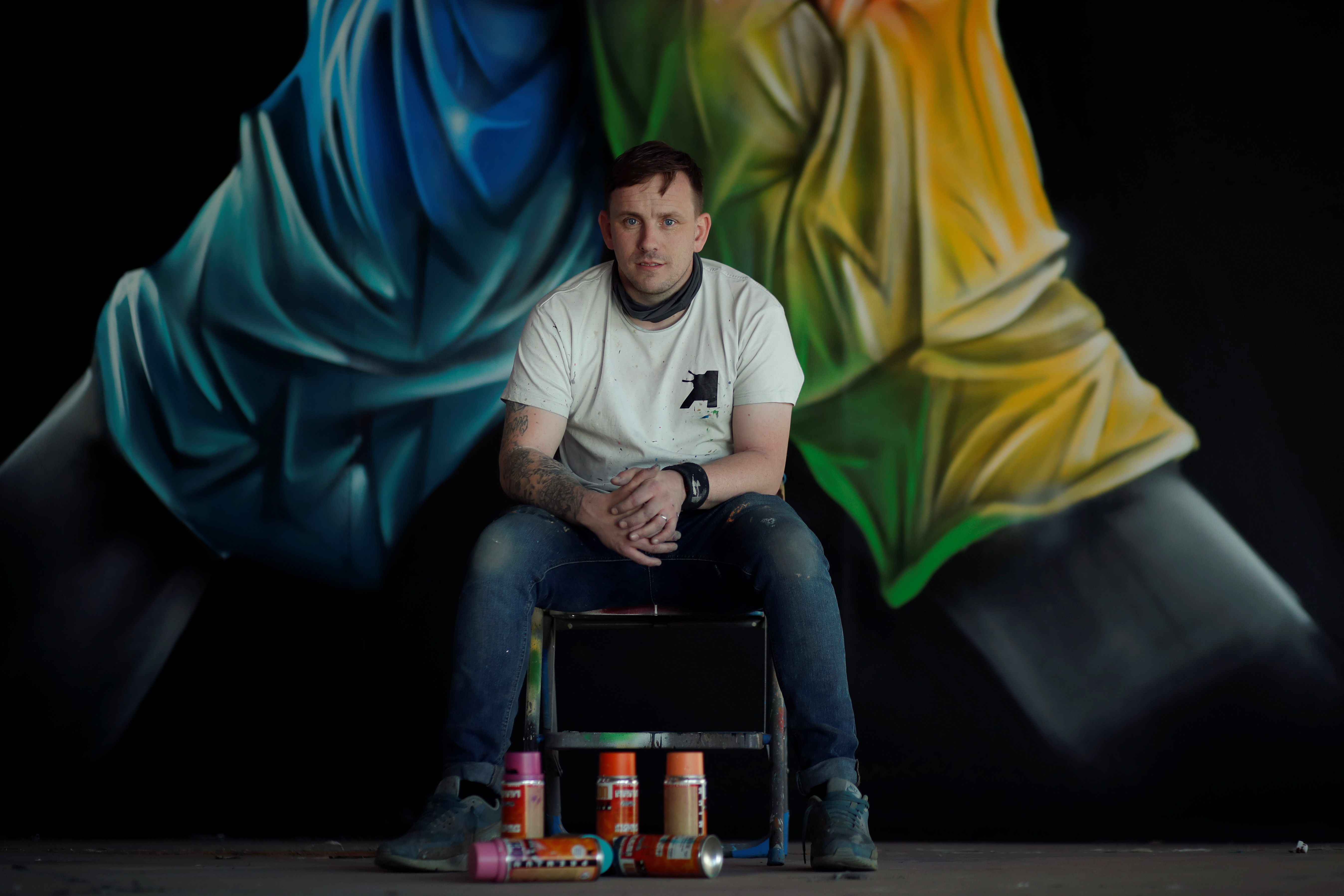 Street artist Nathan Murdoch poses for a picture in front of his artwork after he creates a piece of crypto art to be auctioned with proceeds donated to the NHS in Peterborough, Britain, April 15, 2021. REUTERS/Andrew Couldridge