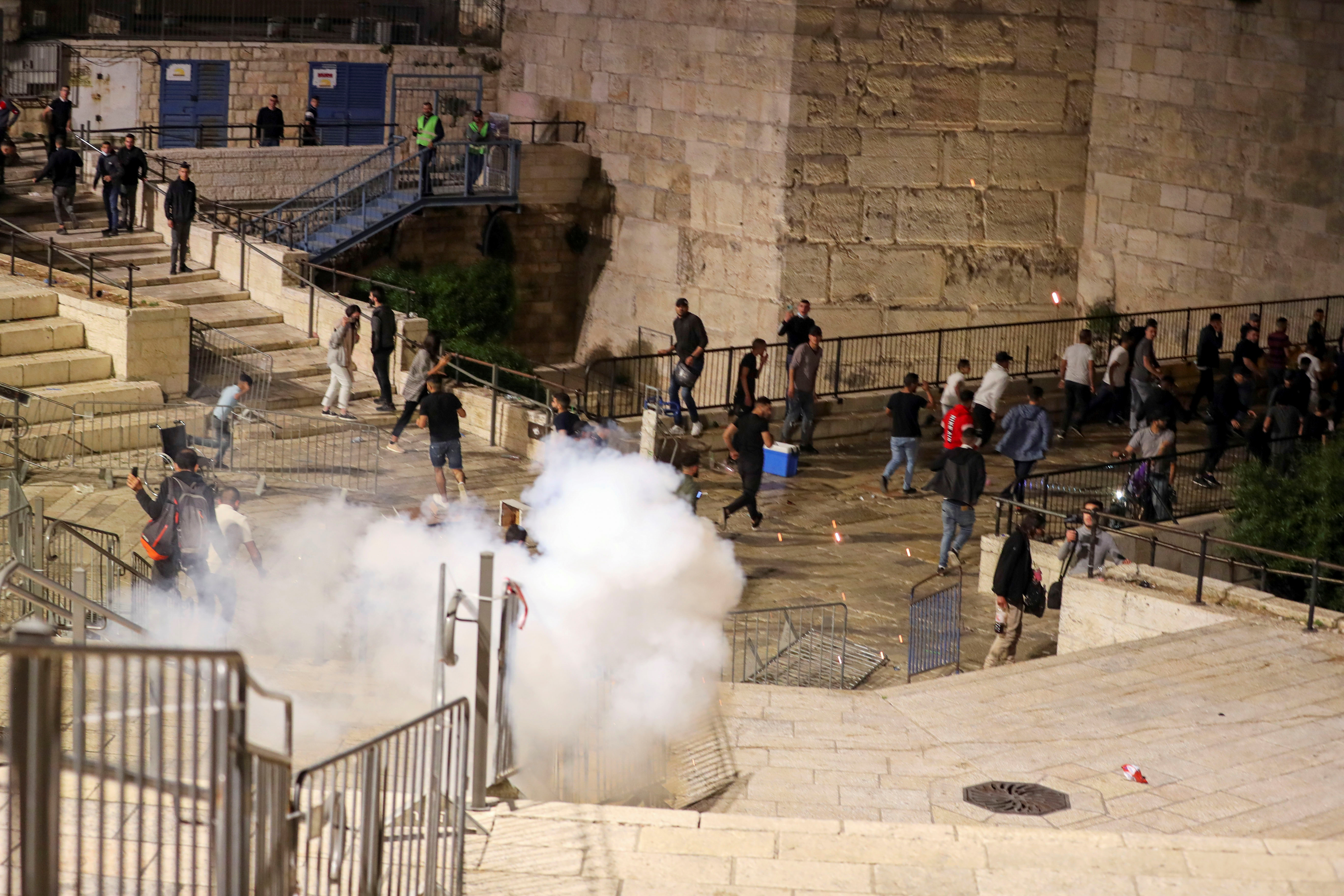 Palestinians run away as a stun grenade fired by Israeli police explodes during clashes at Damascus Gate just outside Jerusalem's Old City, on the Muslim holy fasting month of Ramadan April 17, 2021. Picture taken April 17, 2021. REUTERS/Ammar Awad