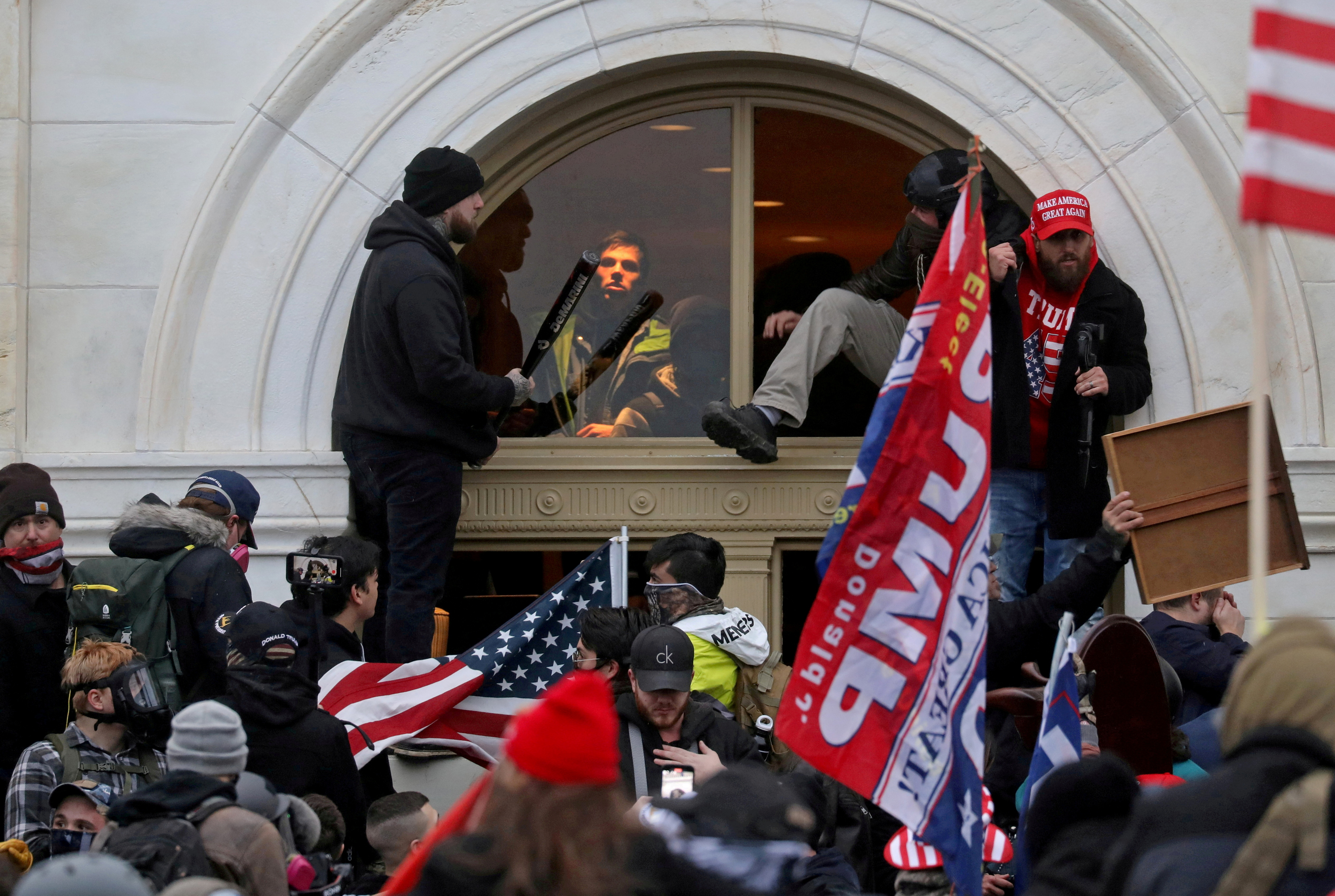 A mob of supporters of then-U.S. President Donald Trump climb through a window they broke as they storm the U.S. Capitol Building in Washington, U.S., January 6, 2021. REUTERS/Leah Millis