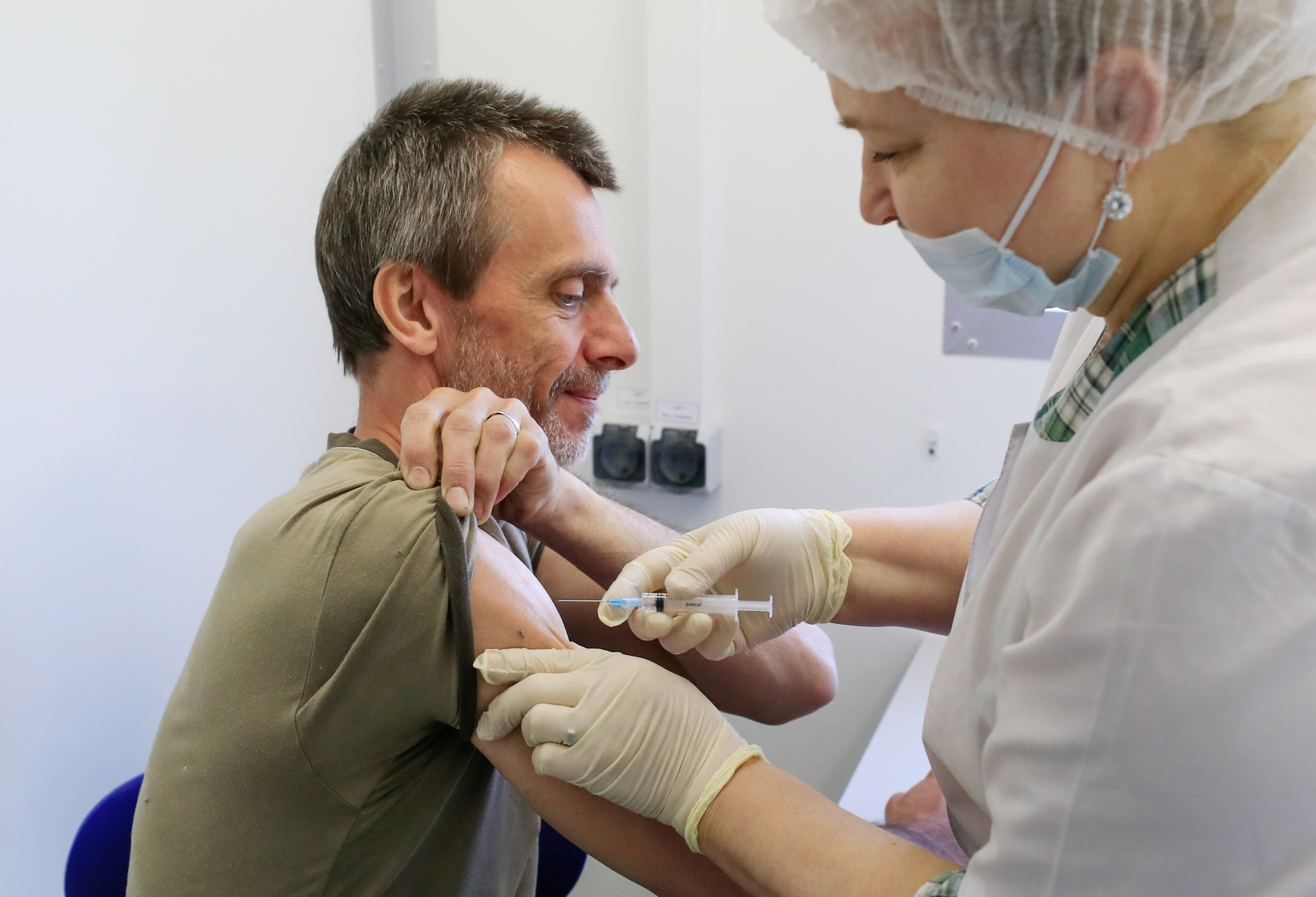 A man receives a dose of Sputnik V (Gam-COVID-Vac) vaccine against the coronavirus disease (COVID-19) at a mobile vaccination centre in a dacha community near the village of Poyarkovo in Moscow Region, Russia May 31, 2021.  REUTERS/Evgenia Novozhenina