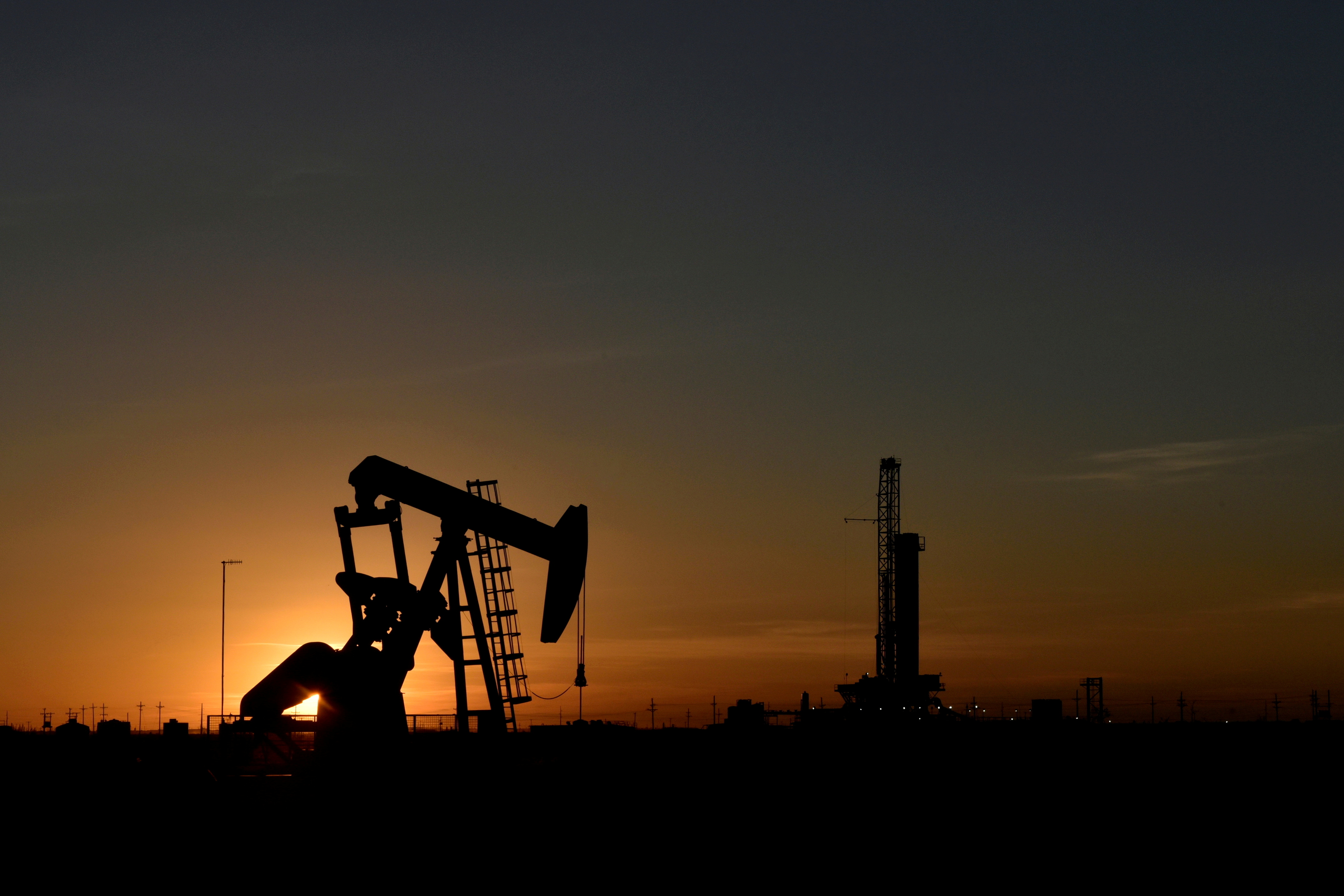 A pump jack operates in front of a drilling rig at sunset in an oil field in Midland, Texas U.S. August 22, 2018. REUTERS/Nick Oxford
