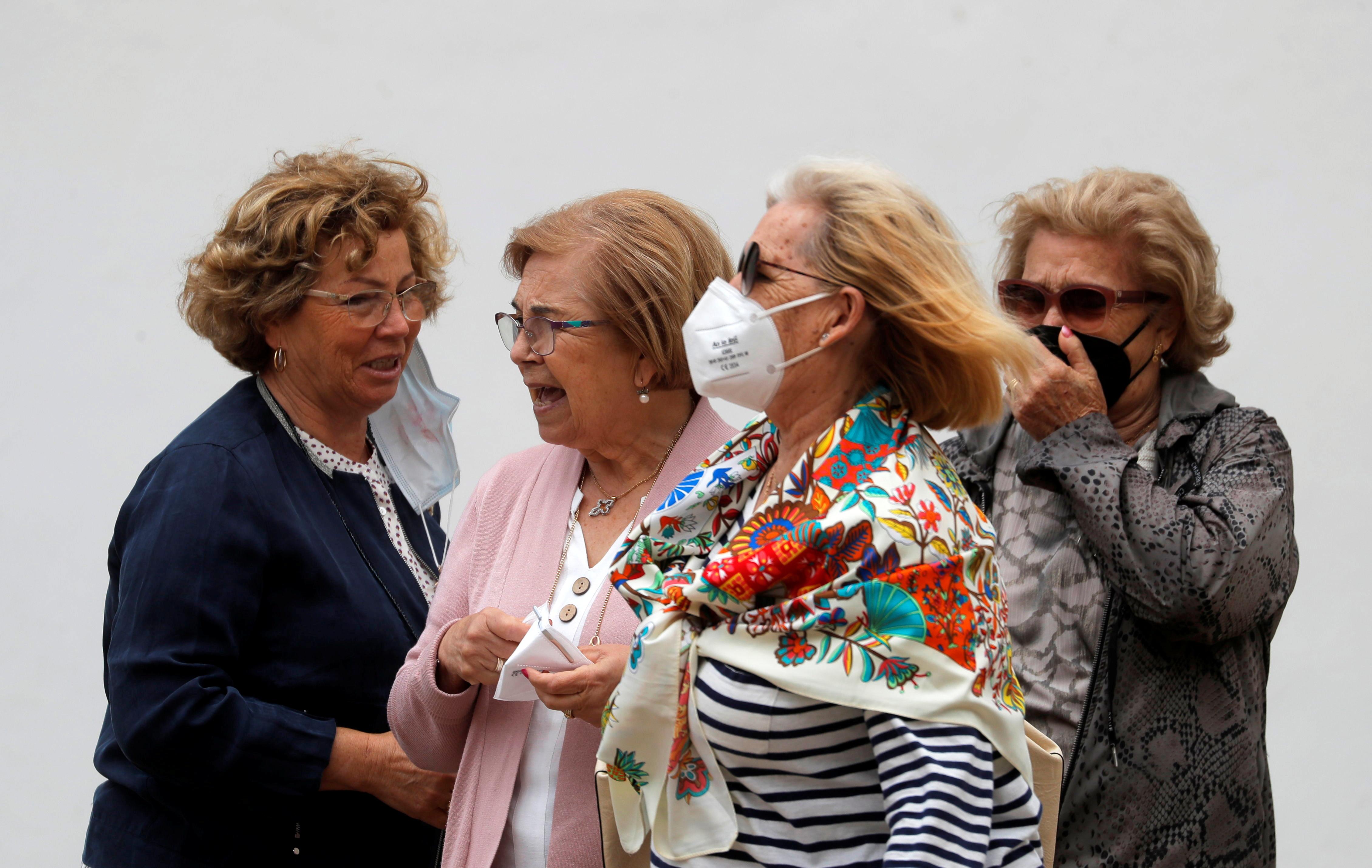 Іспанські туристи знімають захисні маски після того, як сфотографували статую тореадора біля арени для кориди, після того, як прем'єр-міністр Іспанії Педро Санчес заявив у п'ятницю про скасування загального зобов'язання носити маски на відкритому повітрі з 26 червня на тлі коронавірусної хвороби (COVID -19) пандемія, в Ронді, Іспанія, 18 червня 2021 р. REUTERS / Jon Nazca