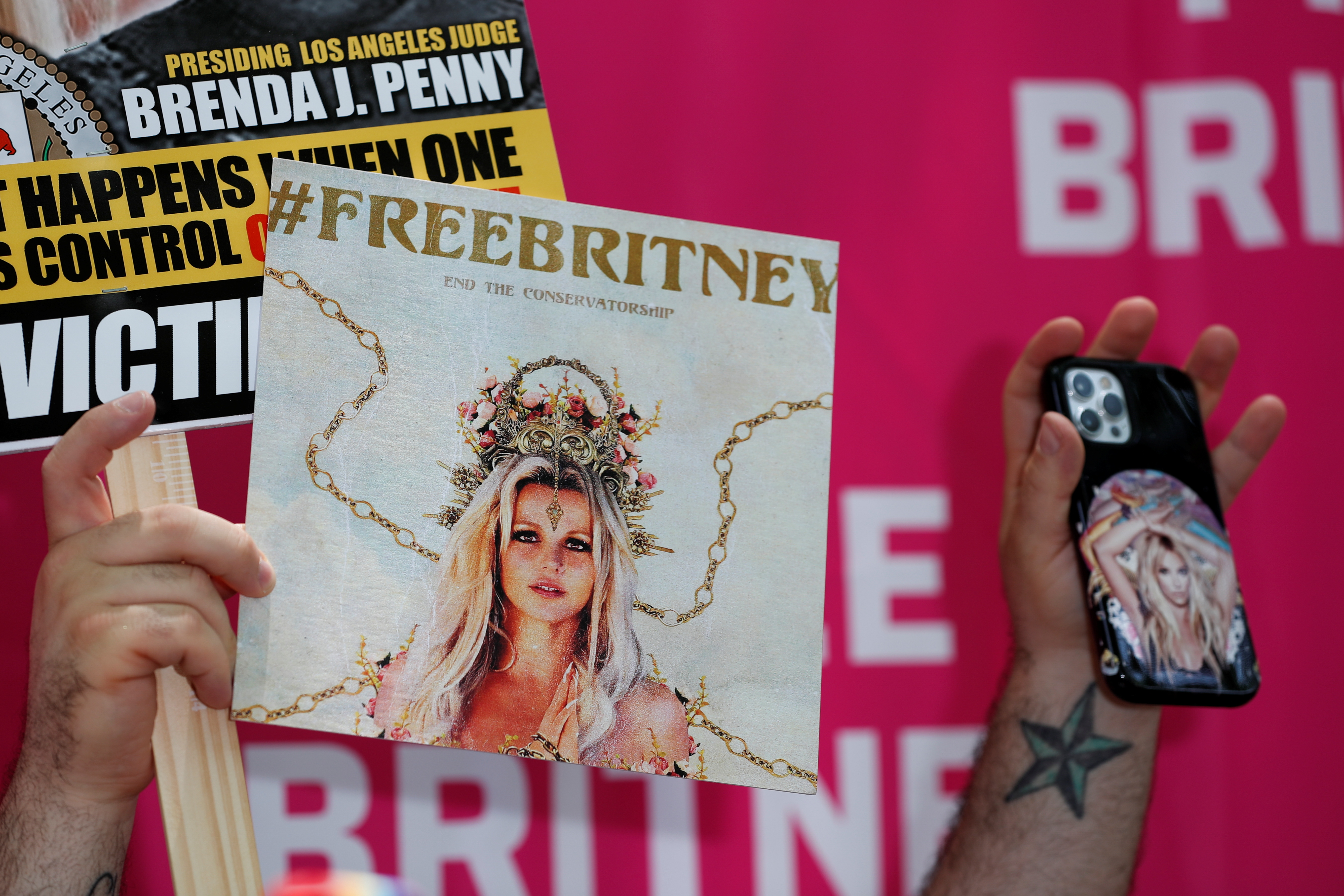 A phone and placards are held during a protest in support of pop star Britney Spears on the day of a conservatorship case hearing at Stanley Mosk Courthouse in Los Angeles, California, U.S., July 14, 2021.  REUTERS/Mario Anzuoni/File Photo
