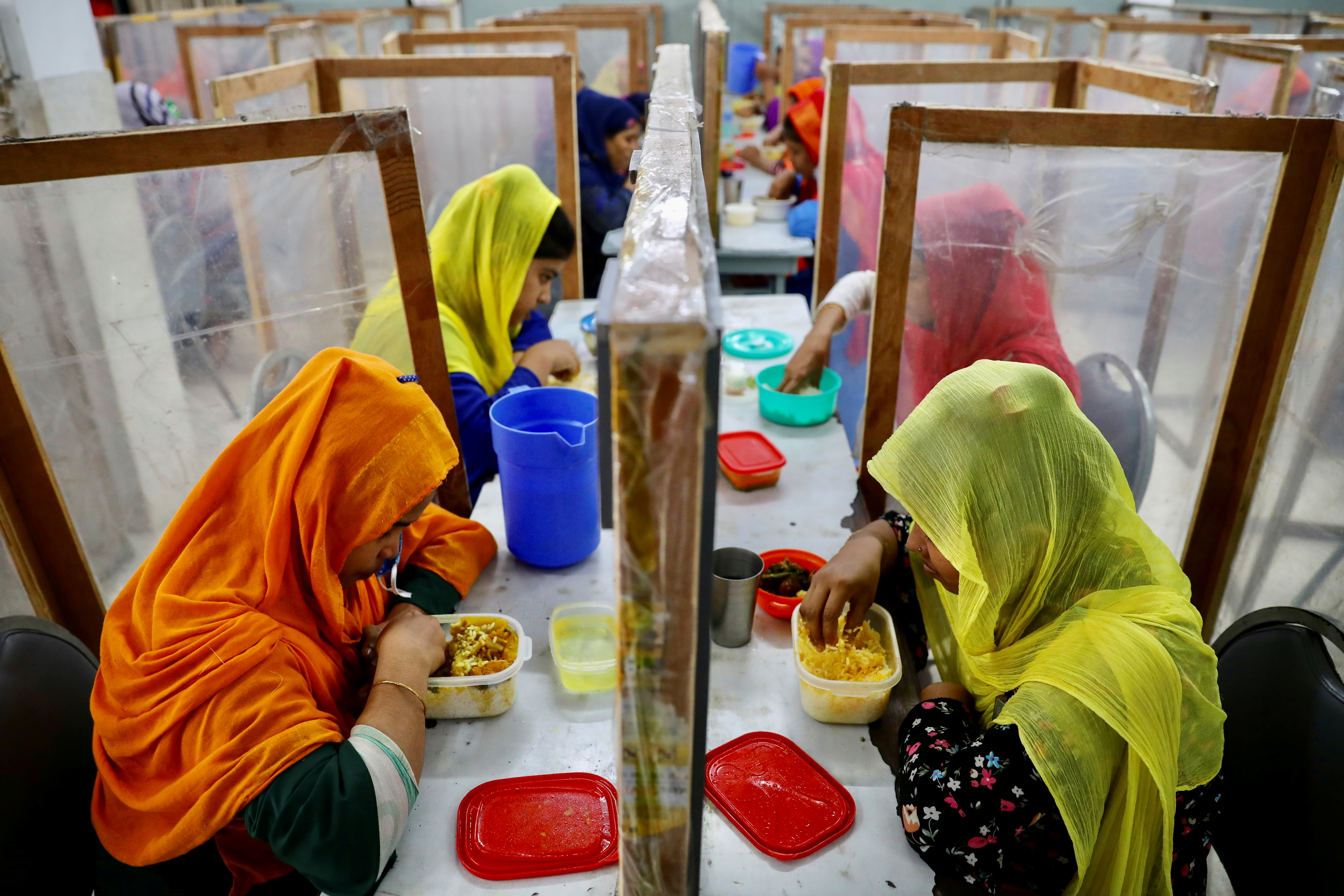 Employees dine between polythene sheets, as a safety measure to reduce the spread of coronavirus disease (COVID-19), at The Civil Engineering Limited garment factory in Dhaka, Bangladesh, August 17, 2021. REUTERS/Mohammad Ponir Hossain     TPX IMAGES OF THE DAY