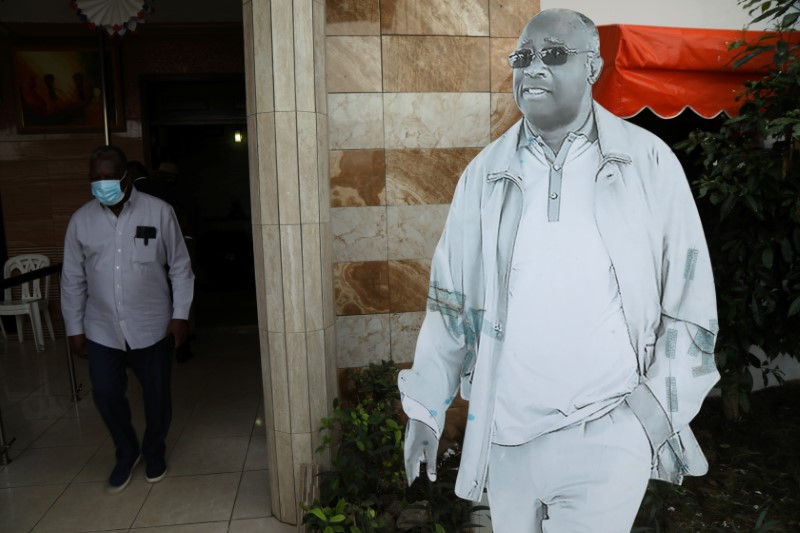 A man walks next to a drawing in relief of former Ivorian President Laurent Gbagbo during the preparation of his return after being acquitted by the International Criminal Court on charges of war crimes, at his party's headquarters in Abidjan, Ivory Coast June 14, 2021. REUTERS/Luc Gnago