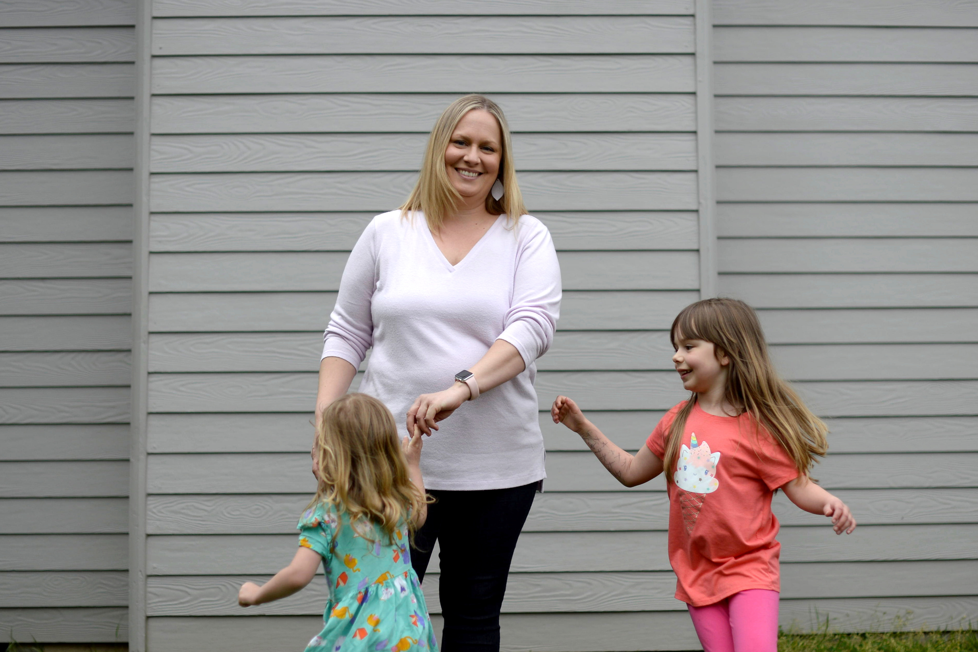Mother of two, Wendy Niculescu, poses for a photo with her daughters Eleanor, left, and Olivia in Tualatin, Oregon, U.S., May 1, 2021. REUTERS/Amanda Lucier