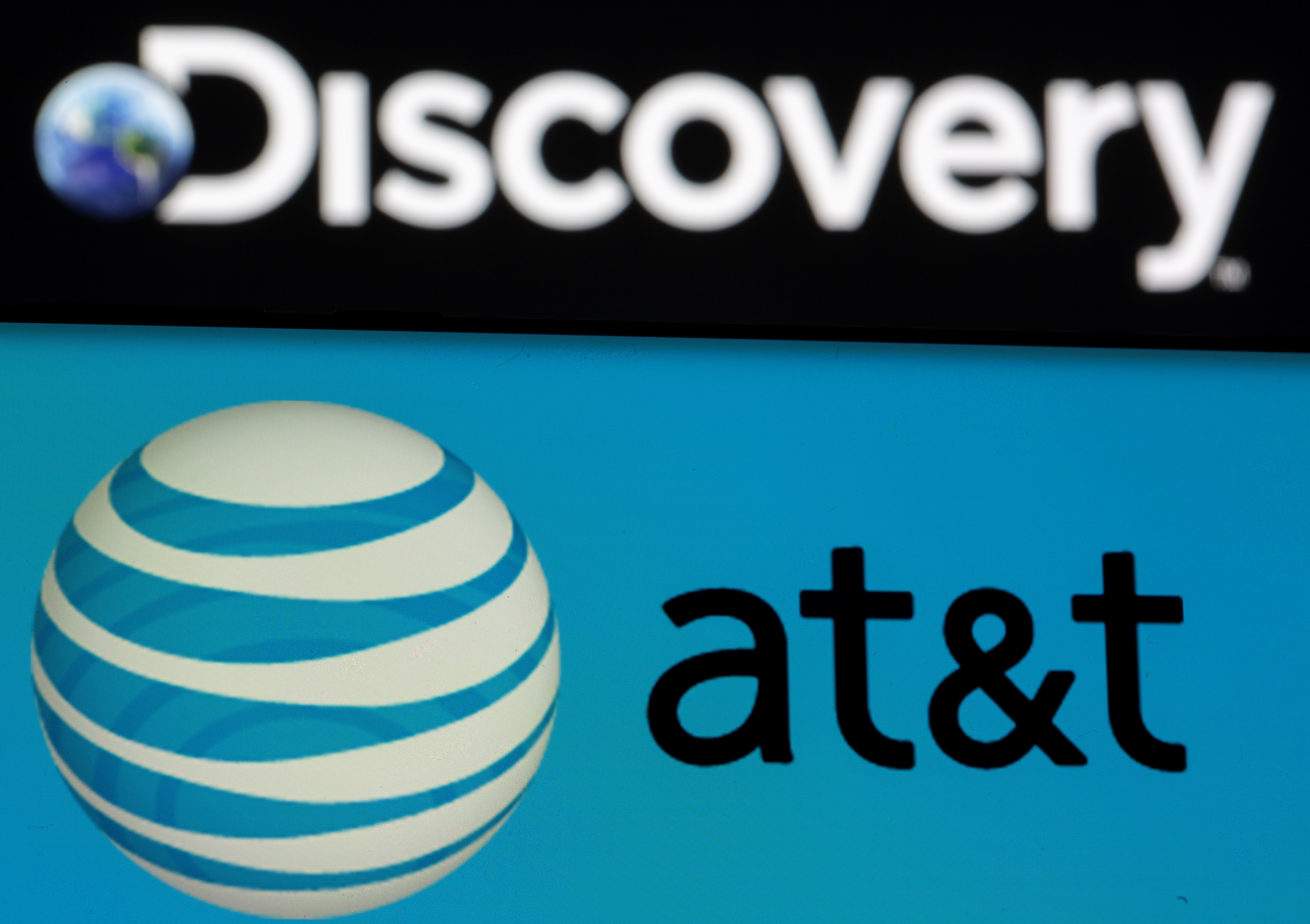 AT&T logo is seen on a smartphone in front of displayed Discovery logo in this illustration taken May 17, 2021. REUTERS/Dado Ruvic