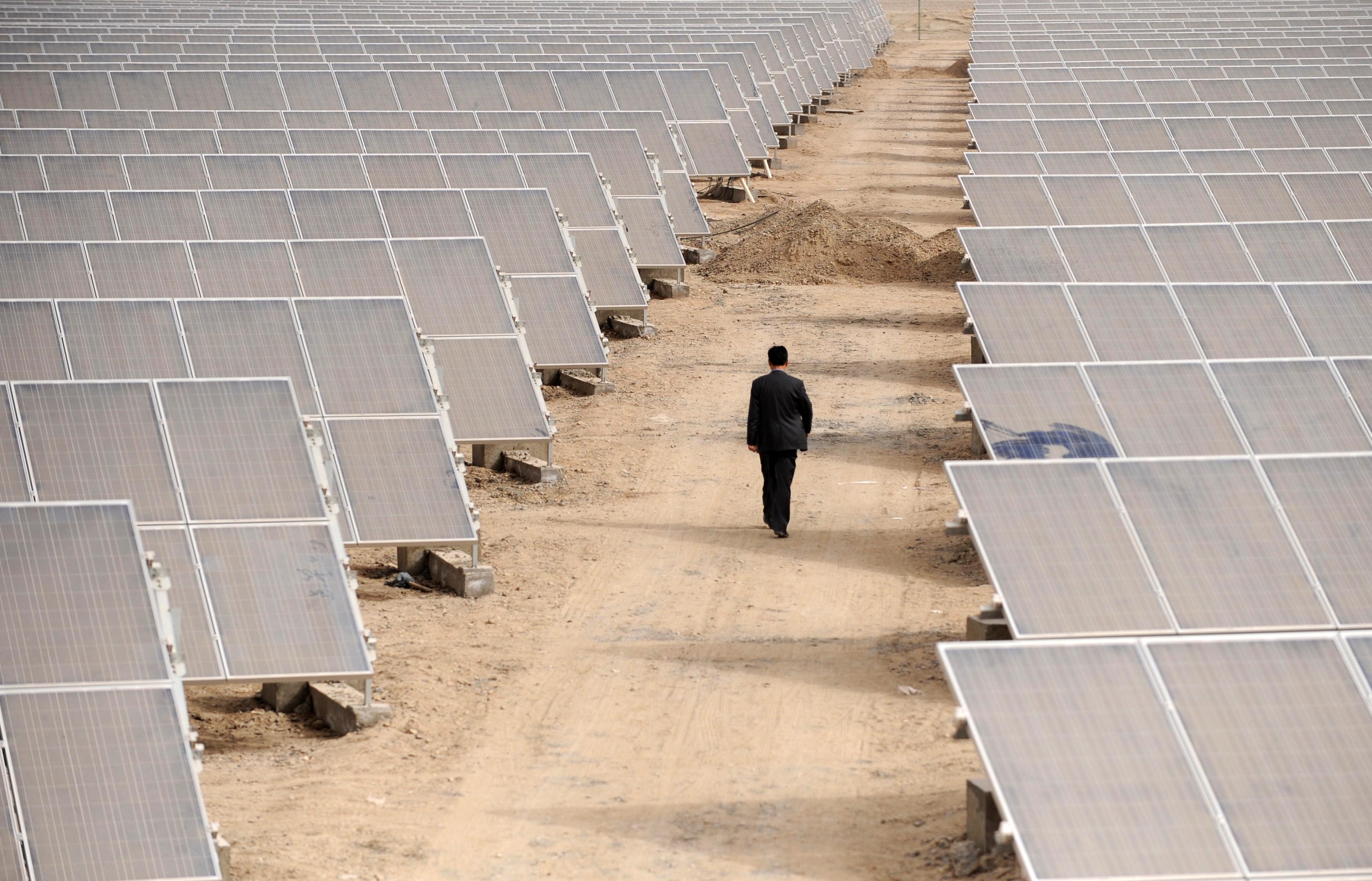 A man walks through solar panels at a solar power plant under construction in Aksu, Xinjiang Uyghur Autonomous Region April 5, 2012. REUTERS/Stringer/File Photo