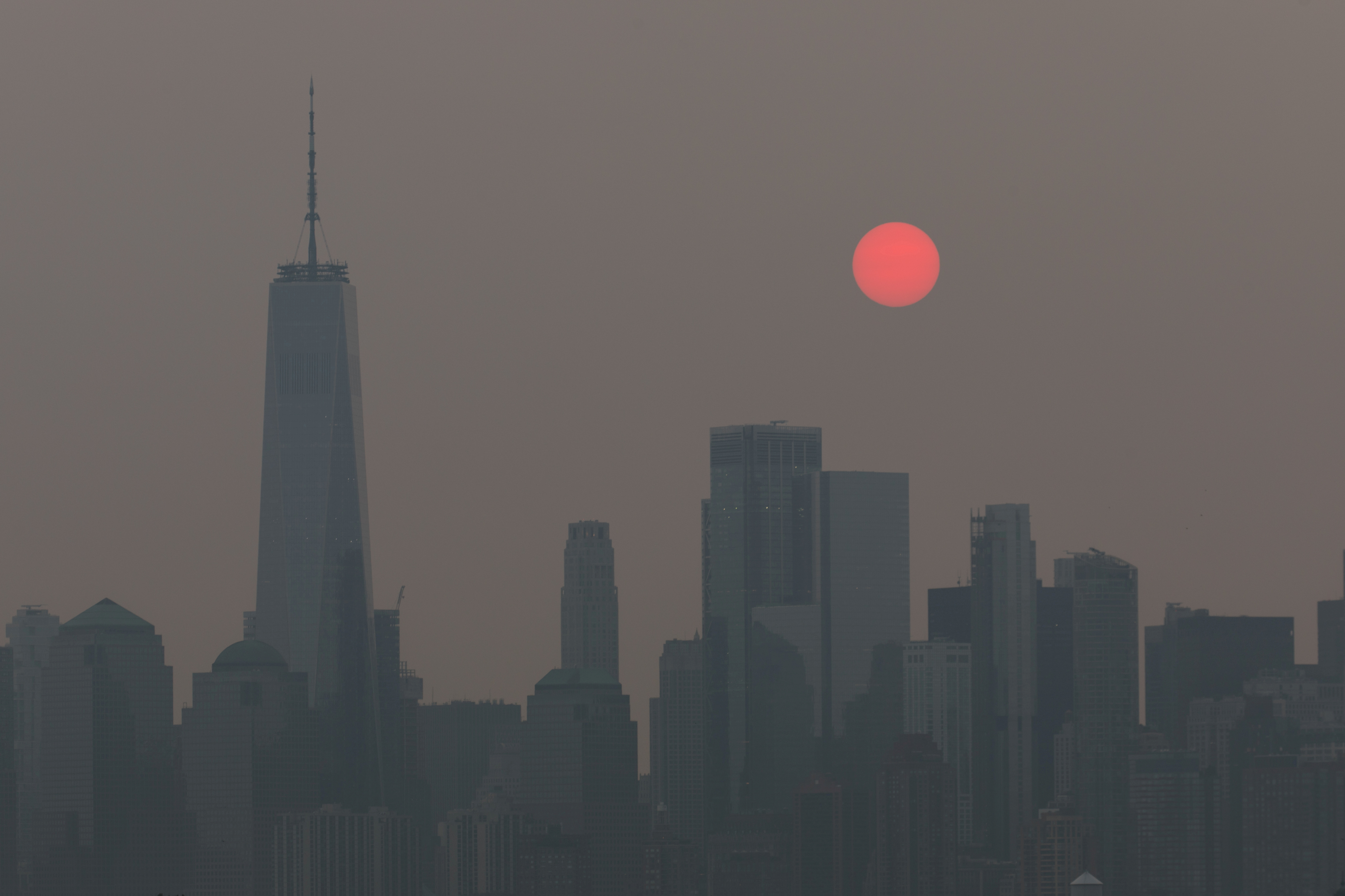 The sun, appearing orange due to smoke haze from forest fires, rises behind the skyline in New York City, New York, U.S., July 21, 2021. REUTERS/Bjoern Kils/New York Media Boat
