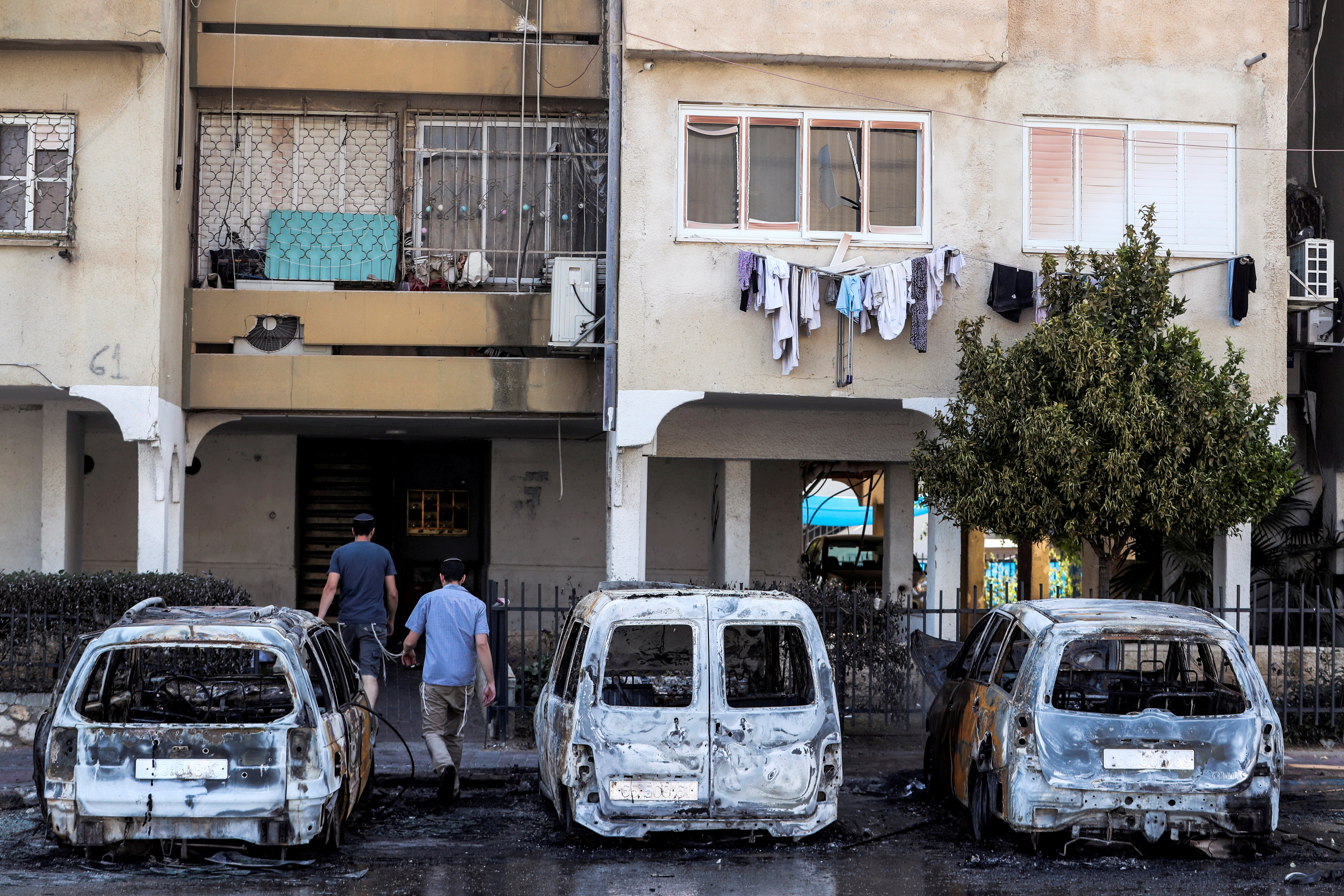 People walk next to burnt vehicles as they enter a building after violent confrontations in the city of Lod, Israel, between Israeli Arab demonstrators and police,  amid high tensions over hostilities between Israel and Gaza militants and tensions in Jerusalem May 12, 2021. REUTERS/Ronen Zvulun