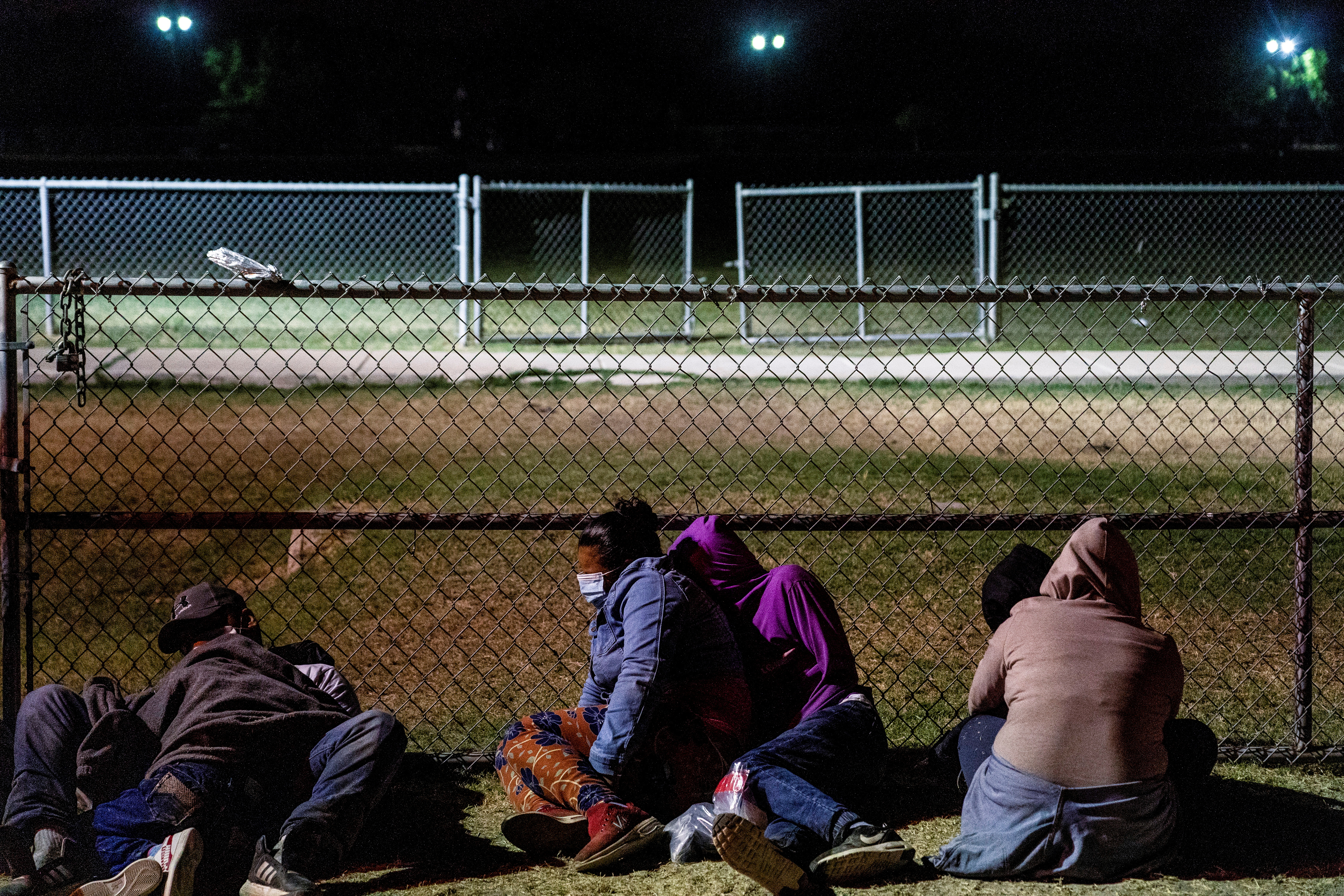 Asylum-seeking migrants' families rest on the ground while waiting to be transported by the U.S. Border Patrols after crossing the Rio Grande River into the United States from Mexico in La Joya, Texas, U.S., April 7, 2021. REUTERS/Go Nakamura/File Photo