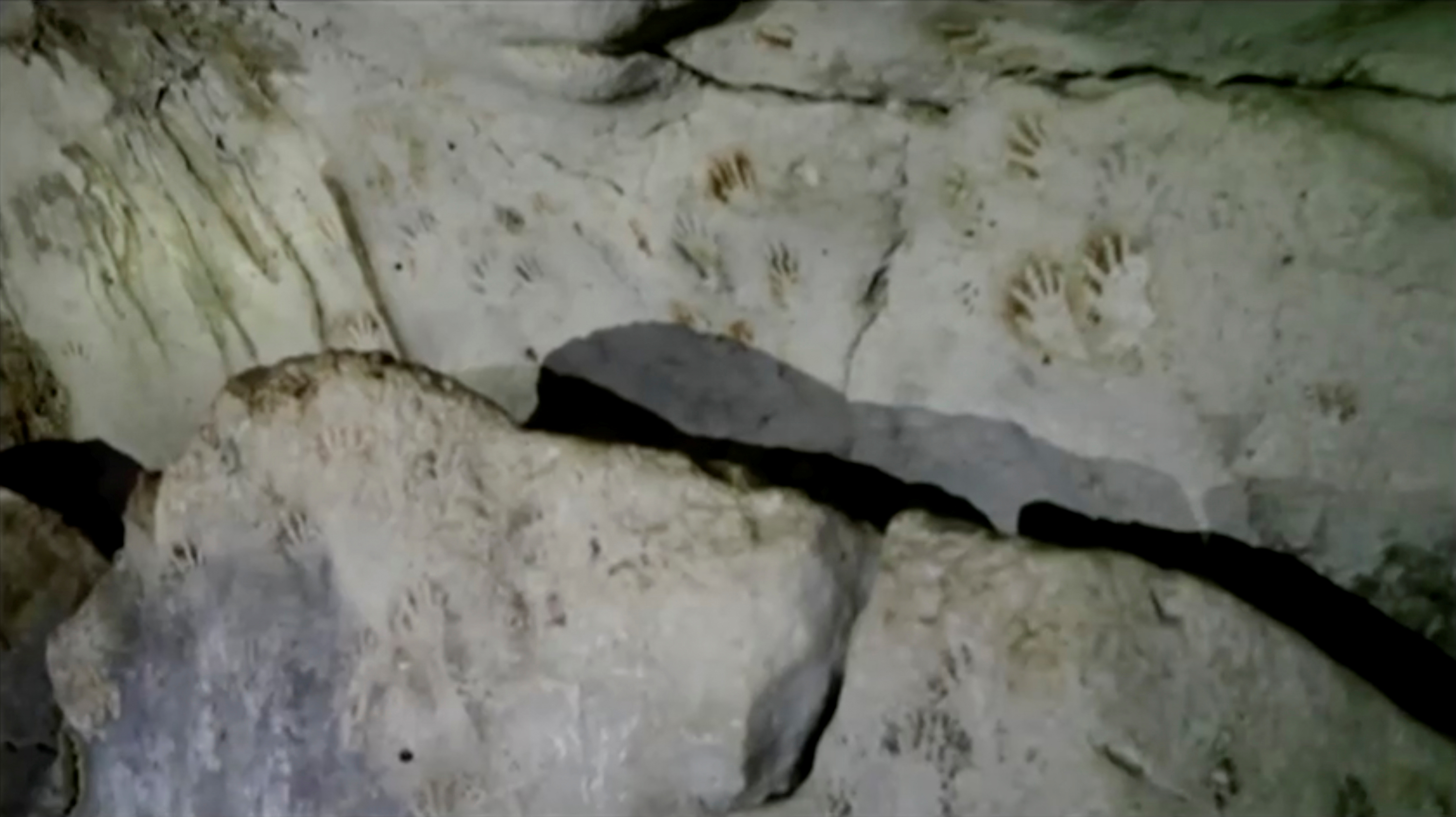 Hand prints, reportedly 1,200 years old, are seen on the cave walls, in Merida, Mexico April 2021, in this screengrab taken from a handout video. SERGIO GROSJEAN/Handout via REUTERS