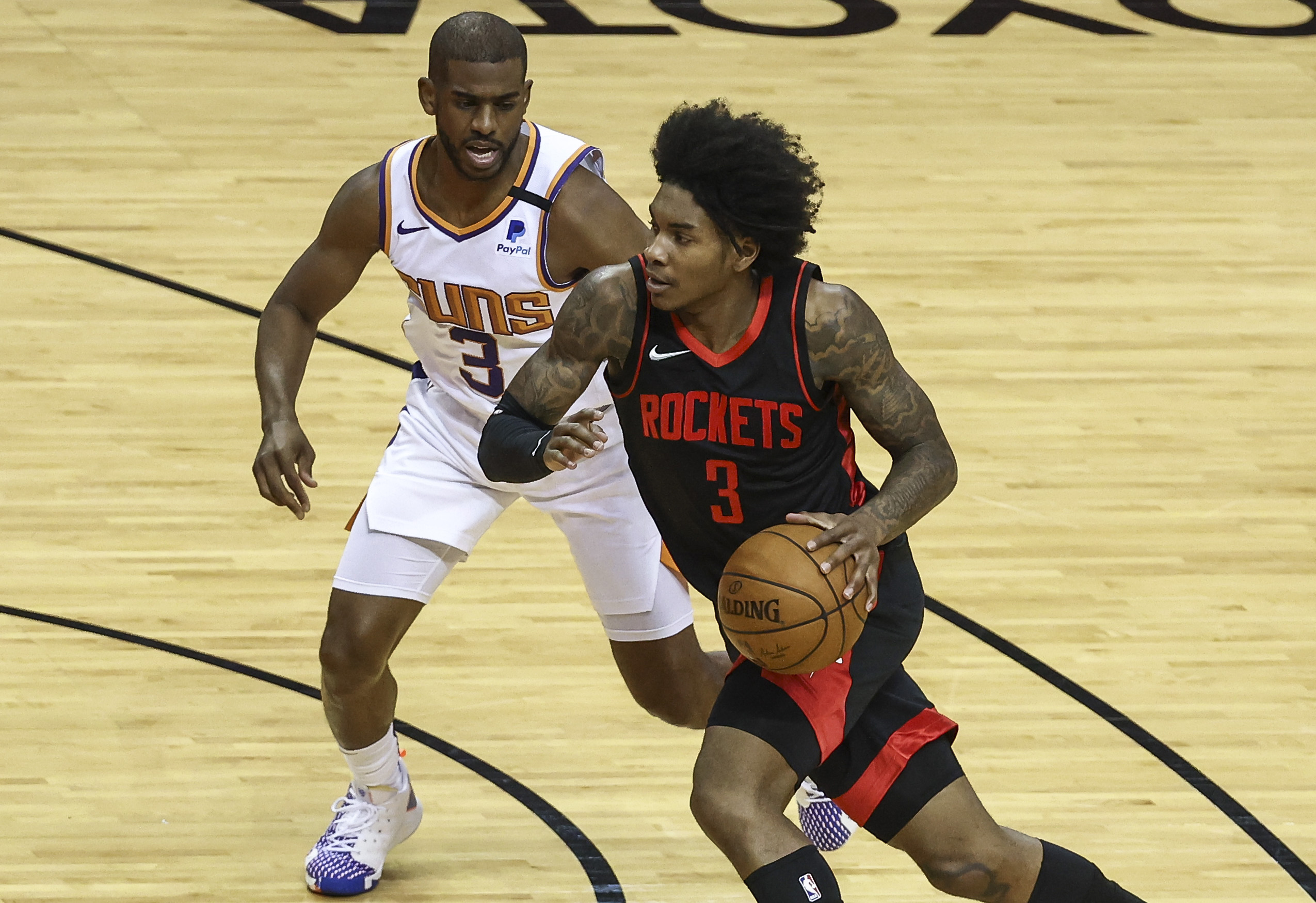 Apr 5, 2021; Houston, Texas, USA; Houston Rockets guard Kevin Porter Jr. (right) dribbles the ball against Phoenix Suns guard Chris Paul (left) during the first quarter at Toyota Center. Mandatory Credit: Troy Taormina-USA TODAY Sports