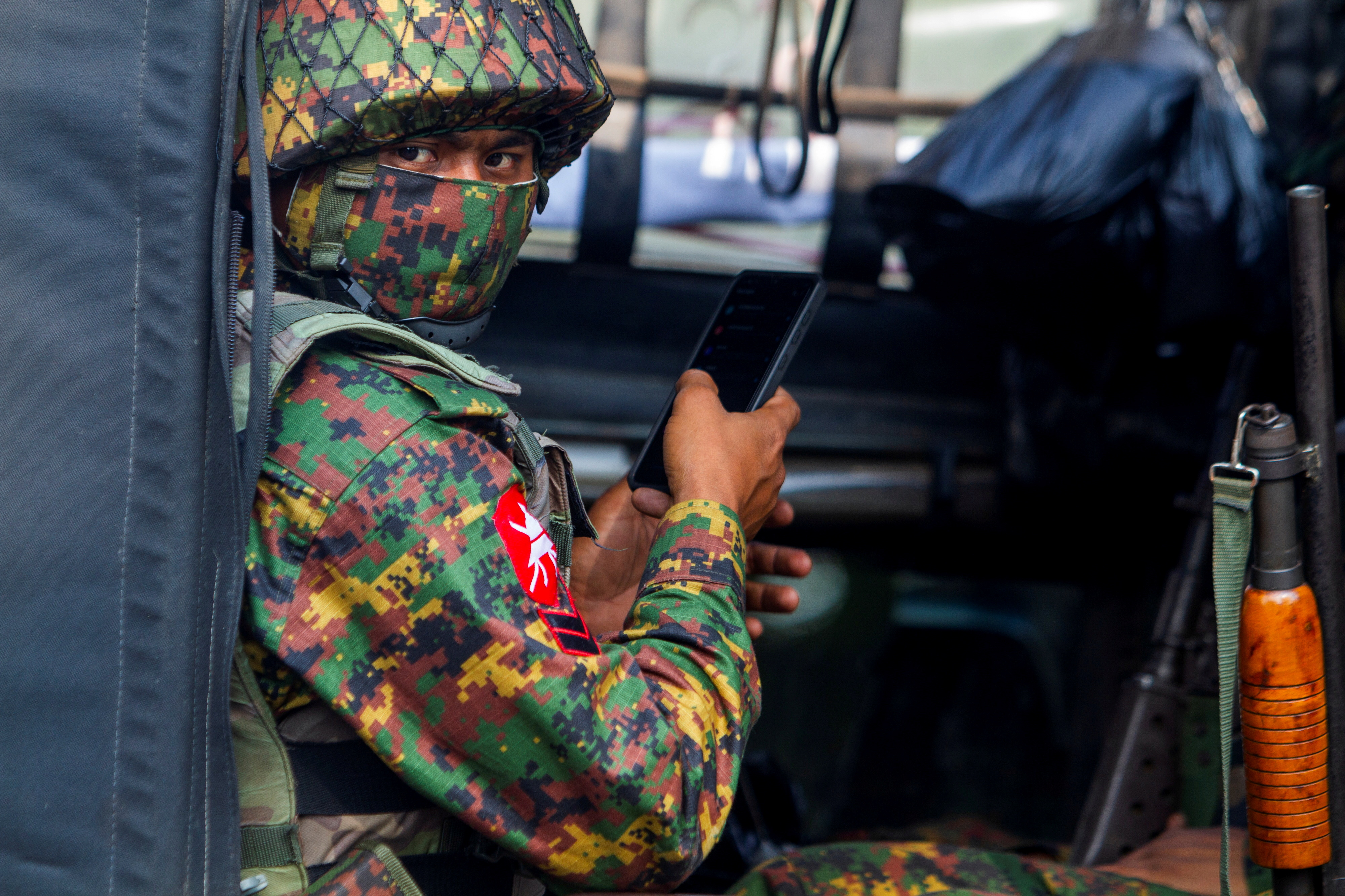 A soldier uses a mobile phone as he sits inside a military vehicle outside Myanmar's Central Bank during a protest against the military coup, in Yangon, Myanmar, February 15, 2021. REUTERS/Stringer