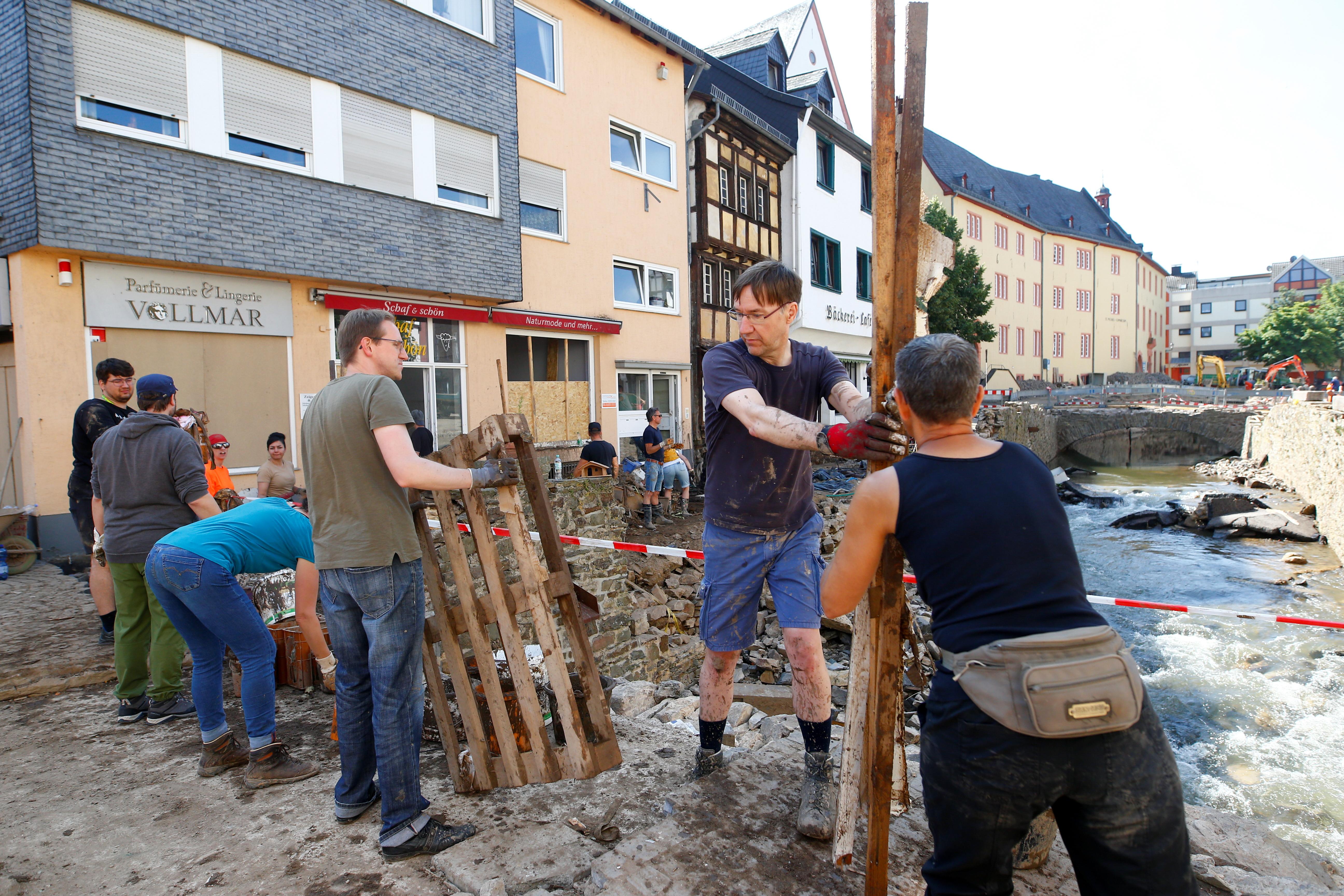 People remove debris and rubbish, following heavy rainfalls, in Bad Muenstereifel, North Rhine-Westphalia state, Germany, July 21, 2021. REUTERS/Thilo Schmuelgen