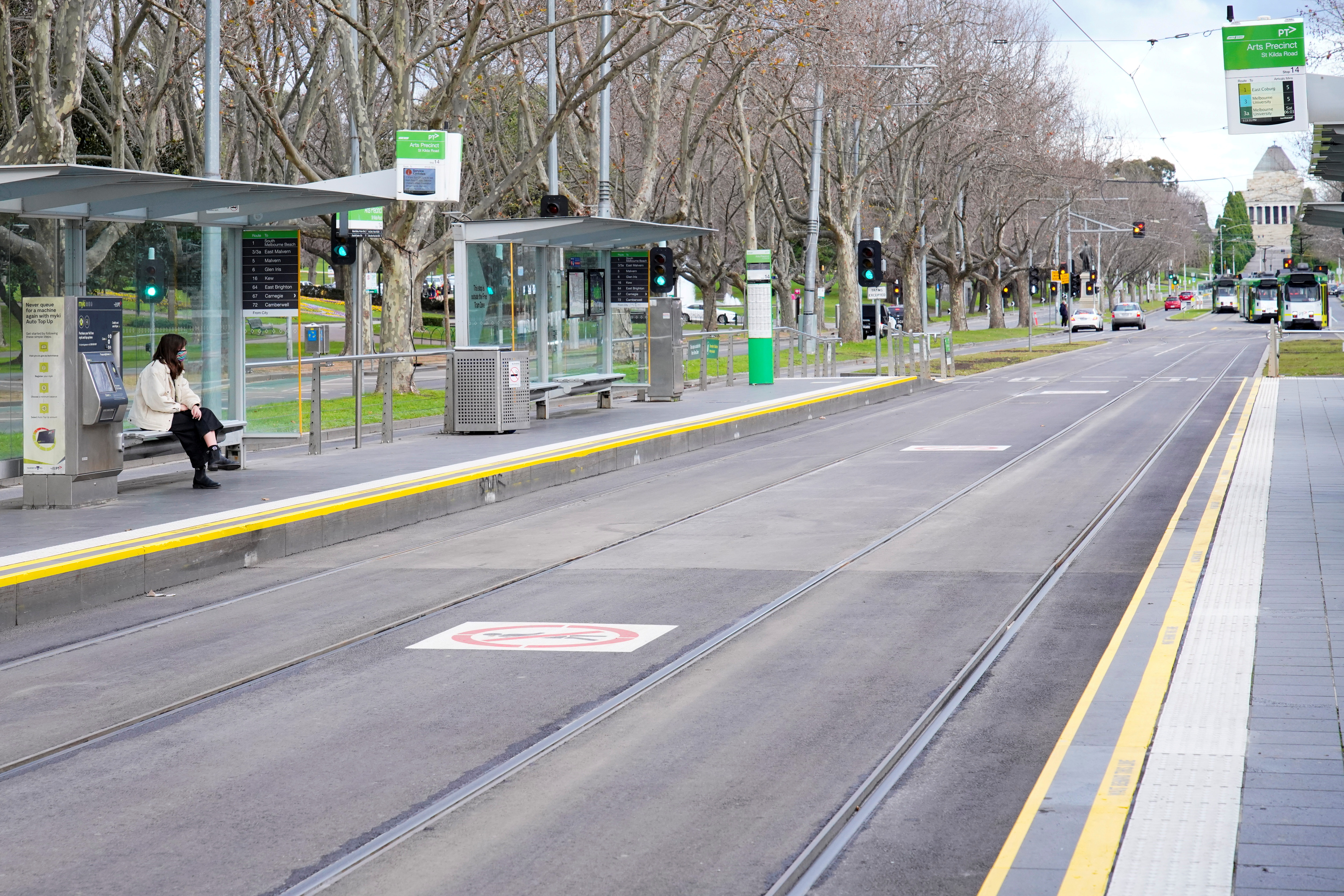 A lone passenger sits at a tram stop on a mostly-empty city centre street on the first day of a lockdown as the state of Victoria looks to curb the spread of a coronavirus disease (COVID-19) outbreak in Melbourne, Australia, July 16, 2021. REUTERS/Sandra Sanders