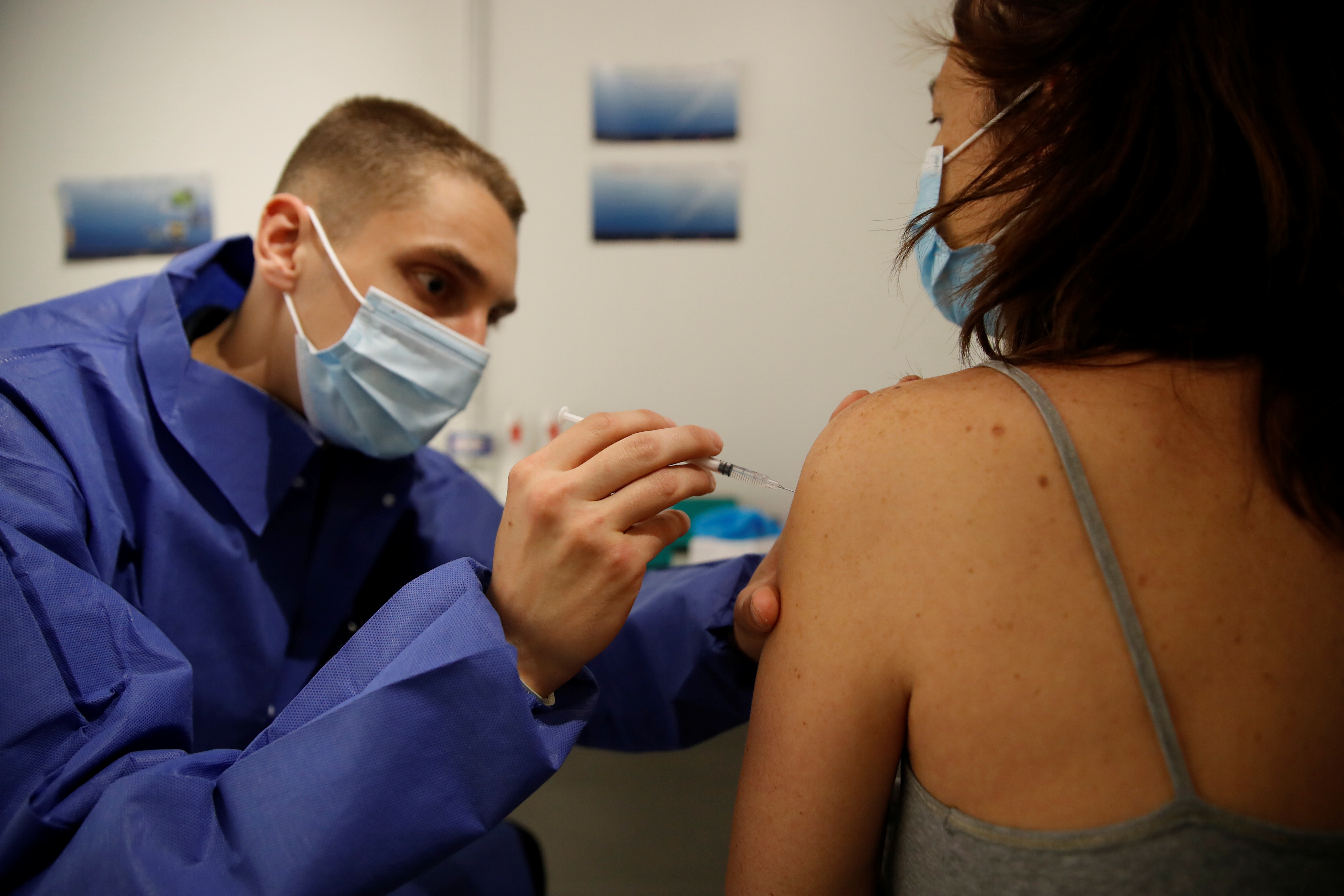 A medical worker administers a dose of the