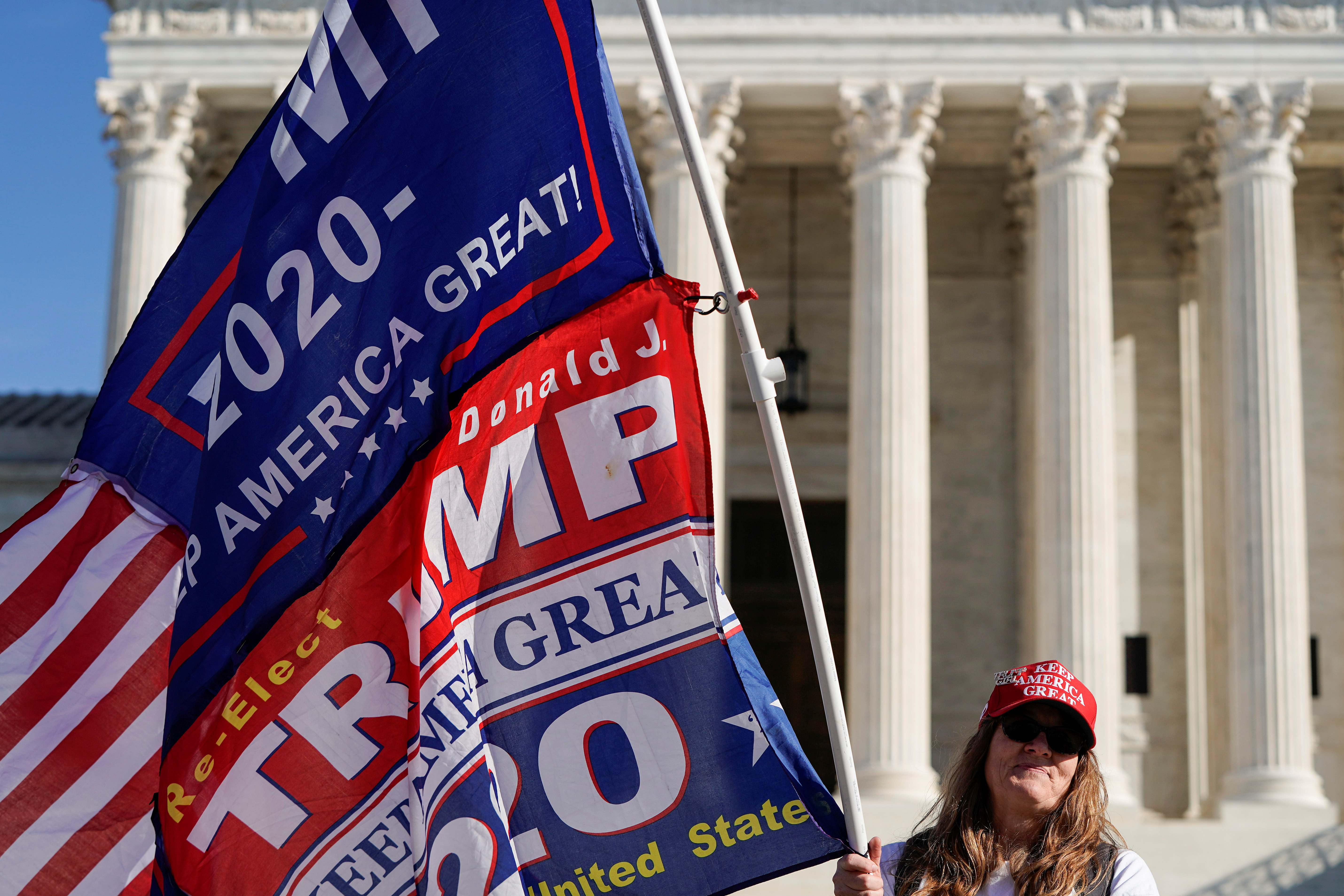 Kathleen Kratt, of Orlando, Florida, and a supporter of U.S. President Donald Trump holds a flag in front of the Supreme Court as the court reviews a lawsuit filed by Texas seeking to undo President-elect Joe Biden's election victory in Washington, U.S., December 11, 2020. REUTERS/Joshua Roberts