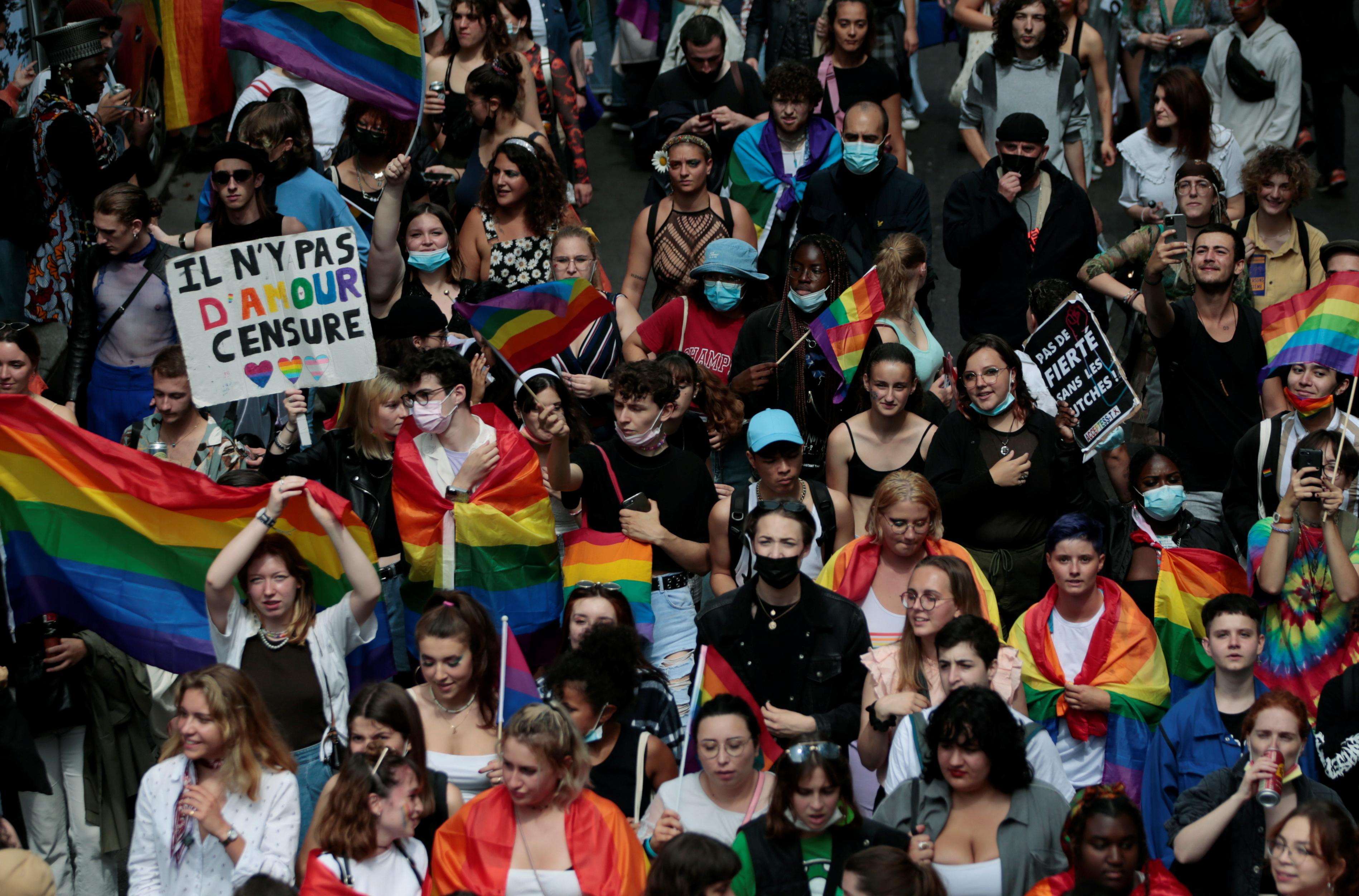 Participantes segurando bandeiras e faixas de arco-íris participam da tradicional marcha do Orgulho LGBTQ, em meio ao surto da doença coronavírus (COVID-19), em Paris, França, em 26 de junho de 2021. REUTERS / Sarah Meyssonnier