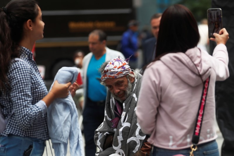 A man sits with a blanket as others take selfies at Times Square in New York City, U.S., June 11, 2021. REUTERS/Shannon Stapleton