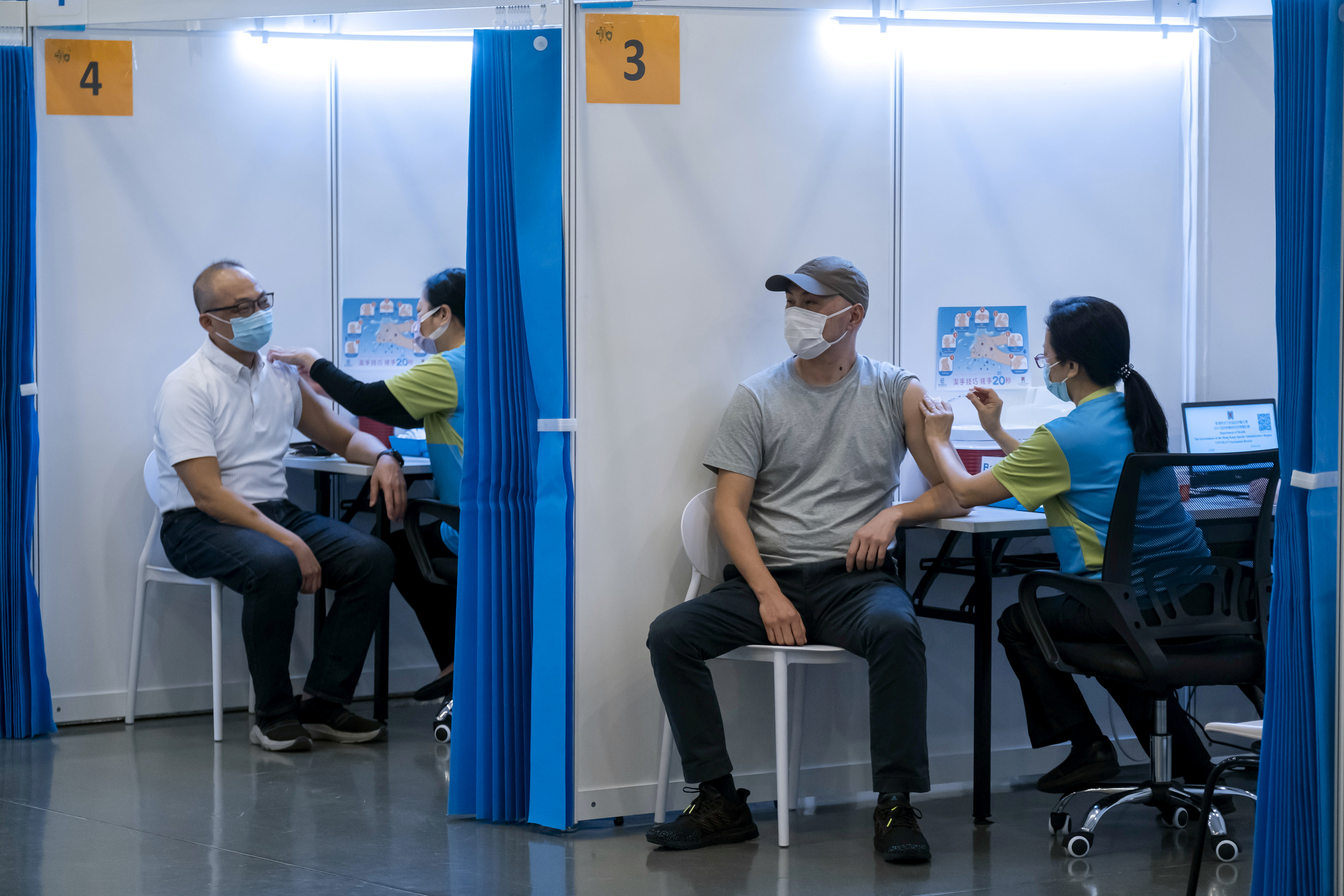 People receive a dose of the Sinovac Biotech's COVID-19 vaccine at a community vaccination center in Hong Kong, China, February 23, 2021. Paul Yeung/Pool via REUTERS