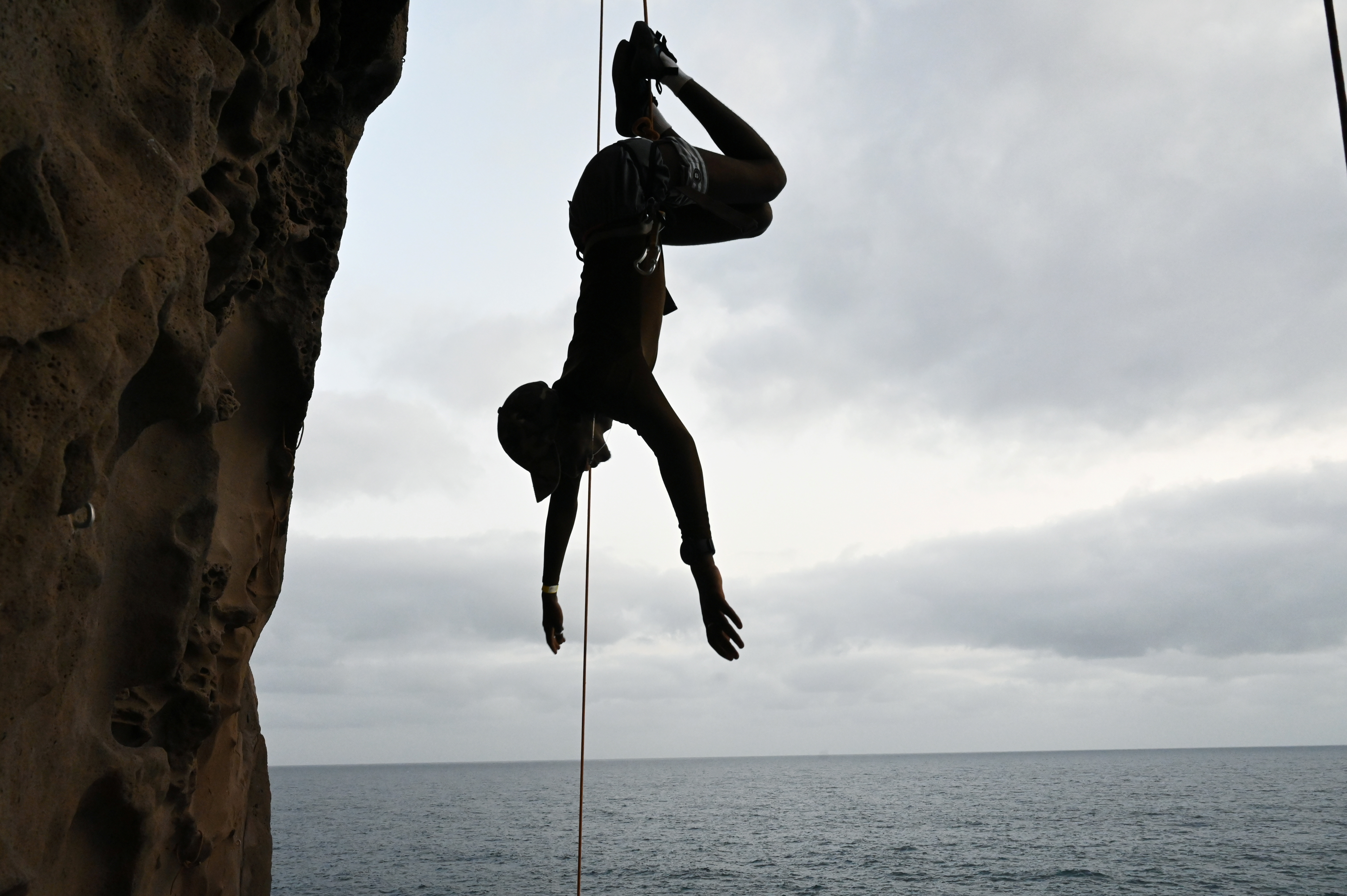 Senegalese rock climber Doudou Diop hangs upside-down from a rope at the Mamelles cliffs in Dakar, Senegal, July 4, 2021. REUTERS/Cooper Inveen